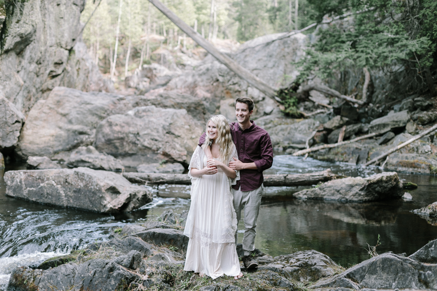 A couple smiles at their waterfall engagement session in the Upper Peninsula of Michigan
