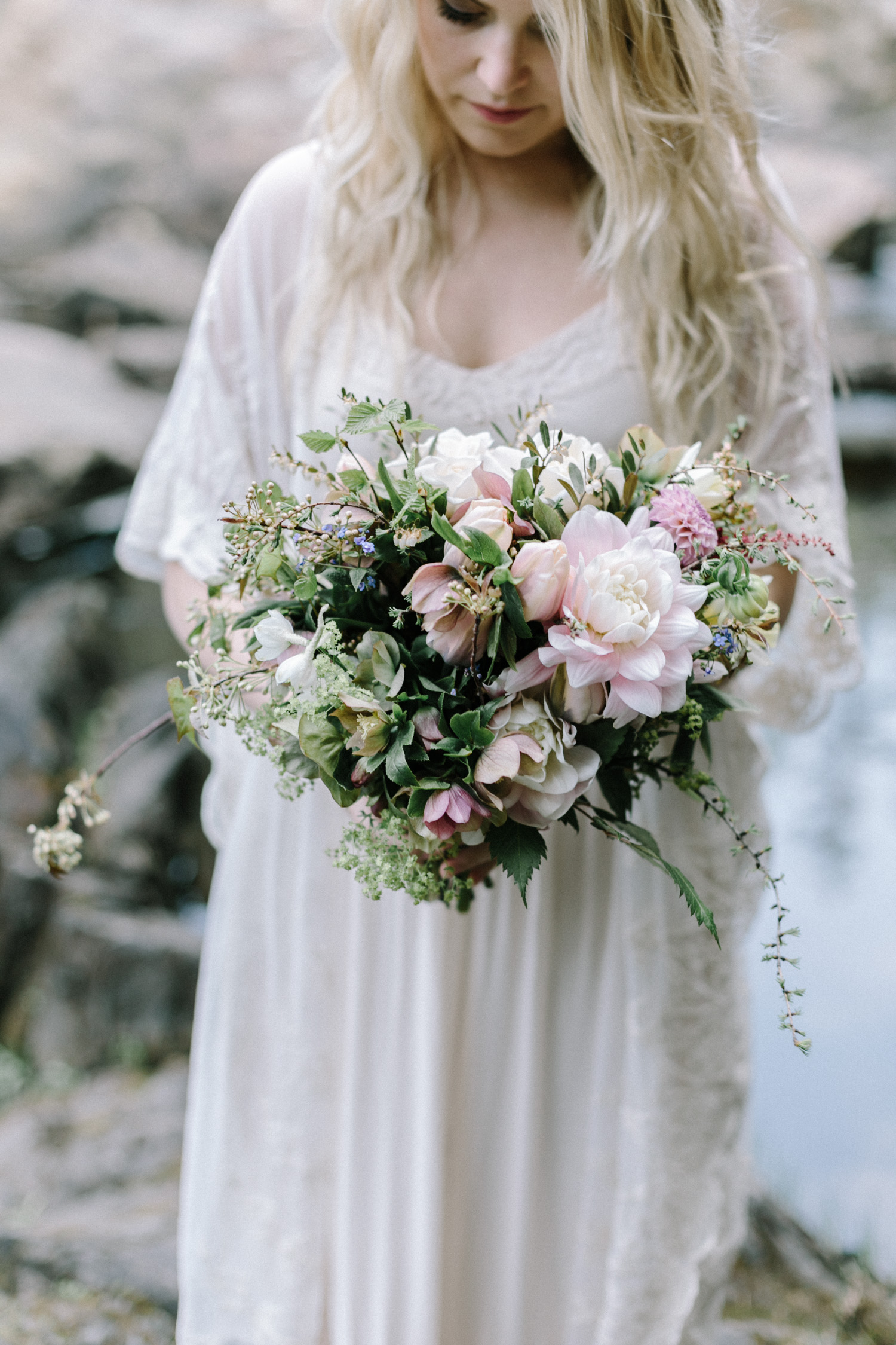 A beautiful woman holds a bouquet made of foraged Michigan flowers in Marquette
