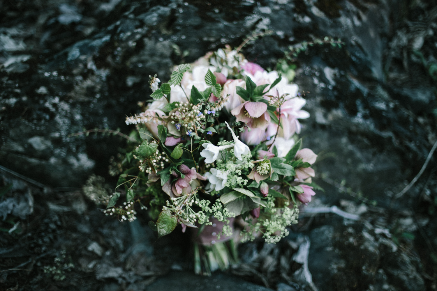 A natural blush and green bouquet of foraged Michigan florals sits on a rock in Marquette, Michigan