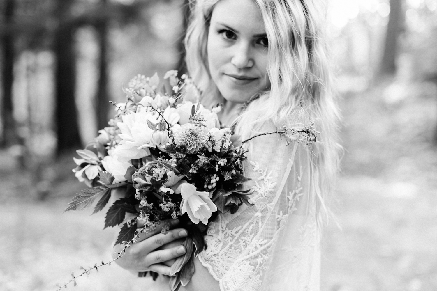 A young blonde woman holds a bouquet at her engagement photo session on film in Marquette, Northern Michigan