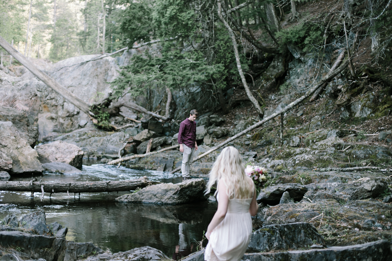 a couple explores and climbs over rocks at a waterfall in Michigan