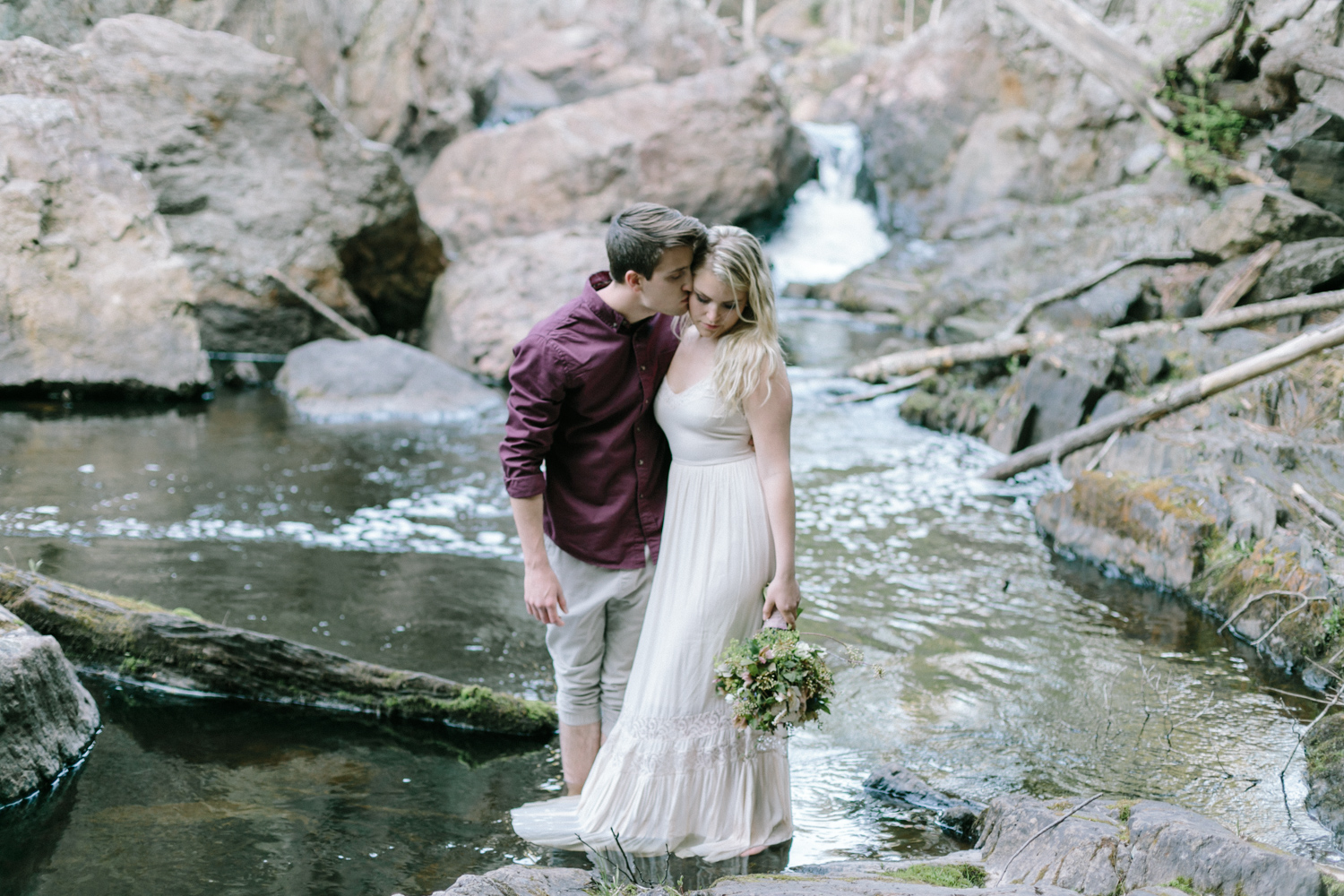 A man kisses his woman at their waterfall engagement session in Northern Michigan