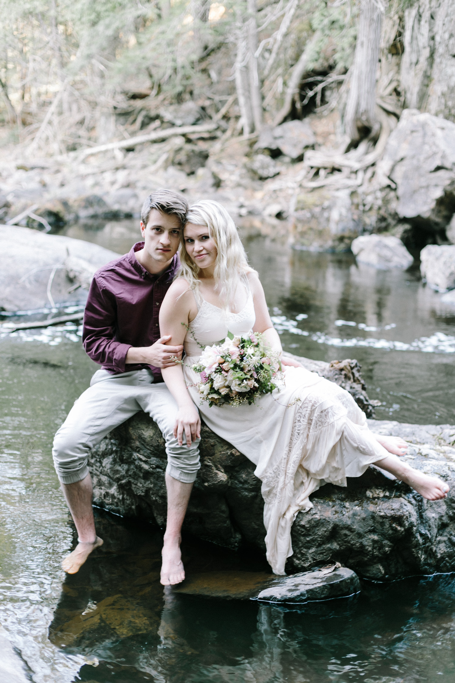 An eloping couple sits on a rock near a waterfall at their Northern Michigan photography session