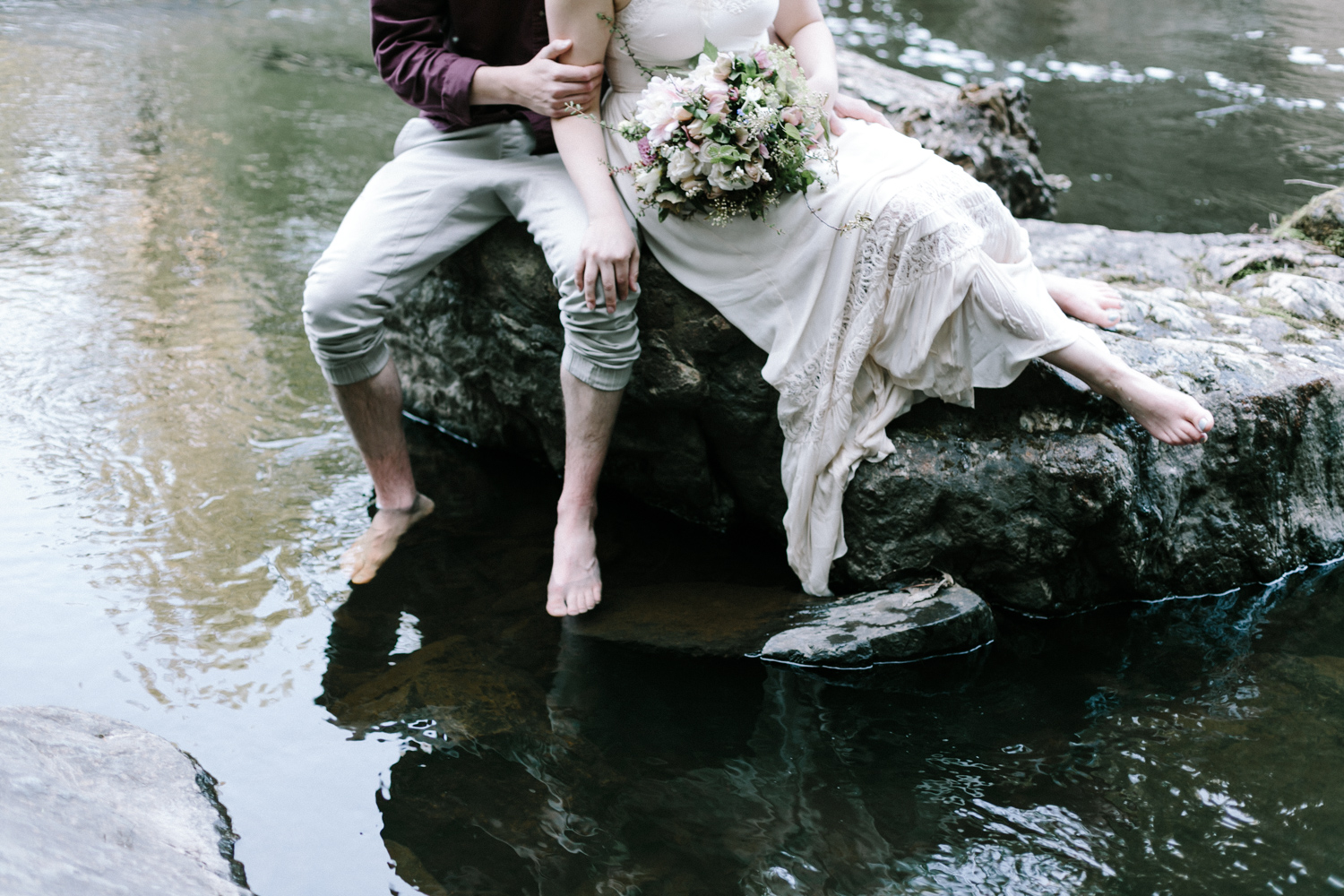 A sits on a rock in the water in Northern Michigan at their elopement photography session with a beautiful bouquet