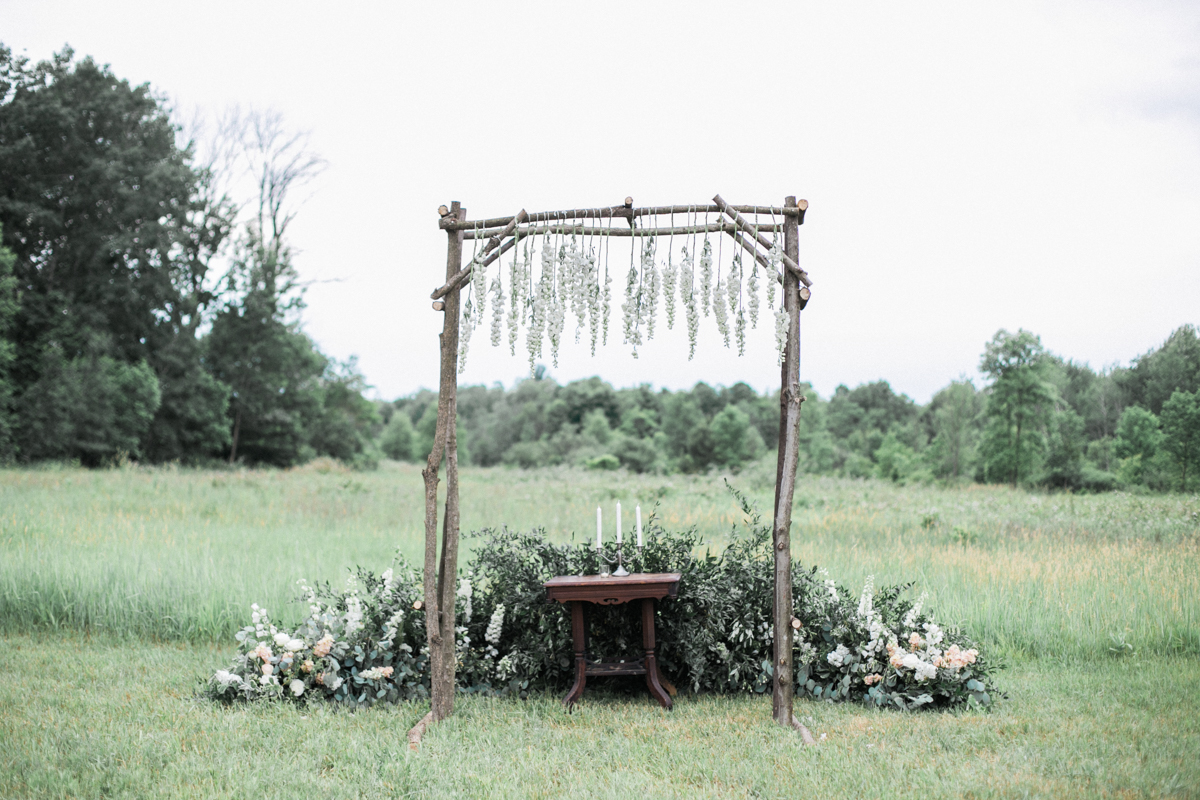 A wood wedding arch sits in a Michigan meadow with hanging lush flowers