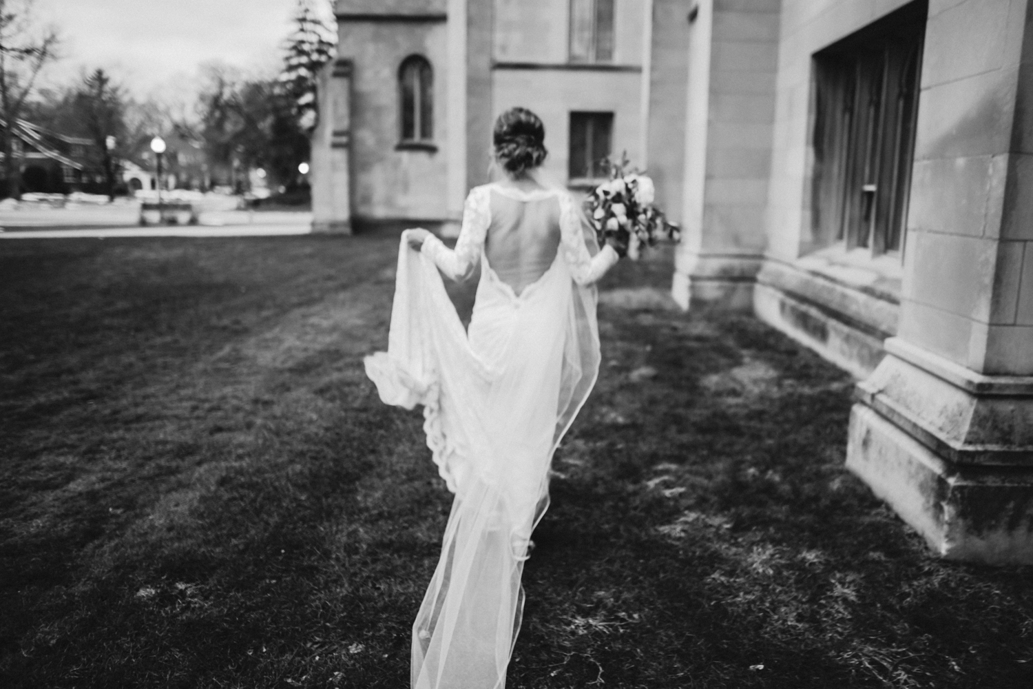 A bride with a beautiful open back wedding gown runs near a cathedral in Holland, Michigan