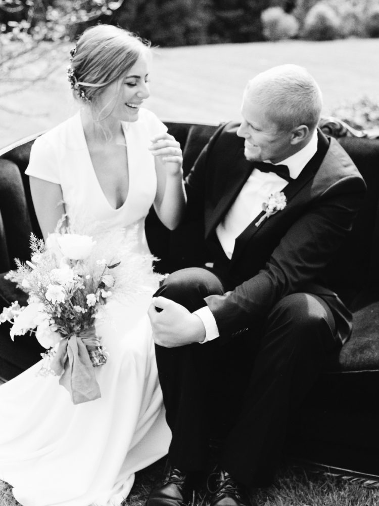 A bride in a simple, elegant wedding gown laughs with her groom on a black velvet couch at their Greencrest Estate wedding in Battle Creek, Michigan