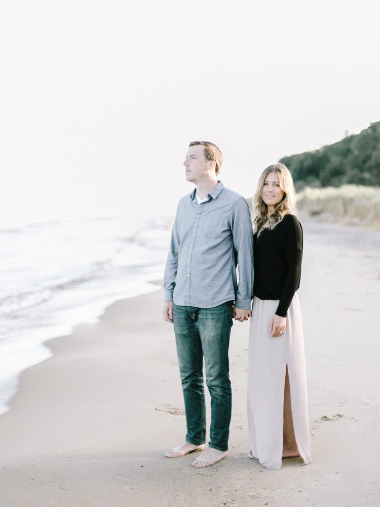a young couple in neutral, casual outfits holding hands on a beach during their engagement film photos in Grand Rapids