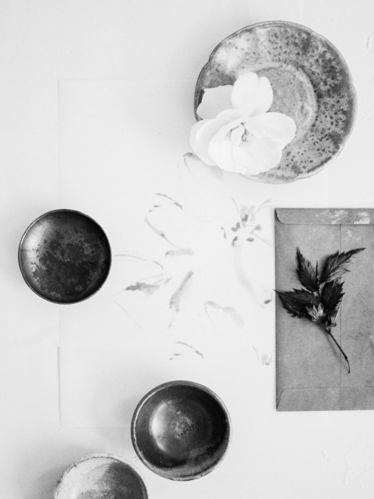 handmade ceramic dishes and a white garden rose rest on a gestural flower illustration in black and white at a Grand Rapids wedding