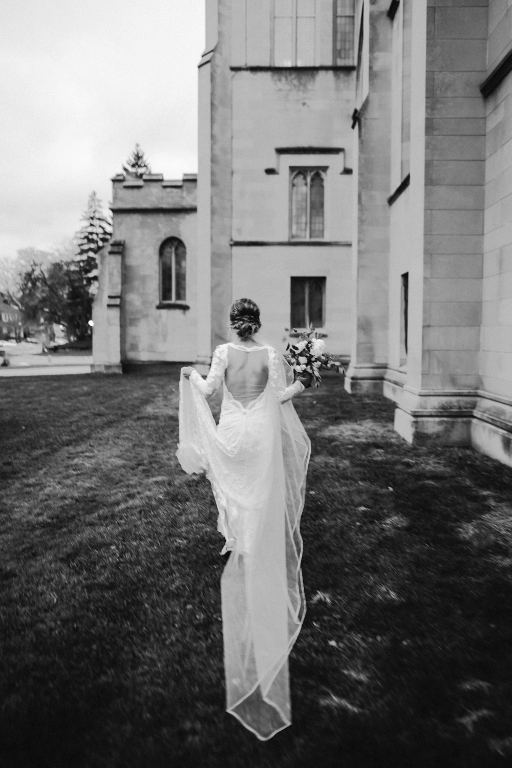 A bride with an open back wedding gown runs near a cathedral in Holland, Michigan