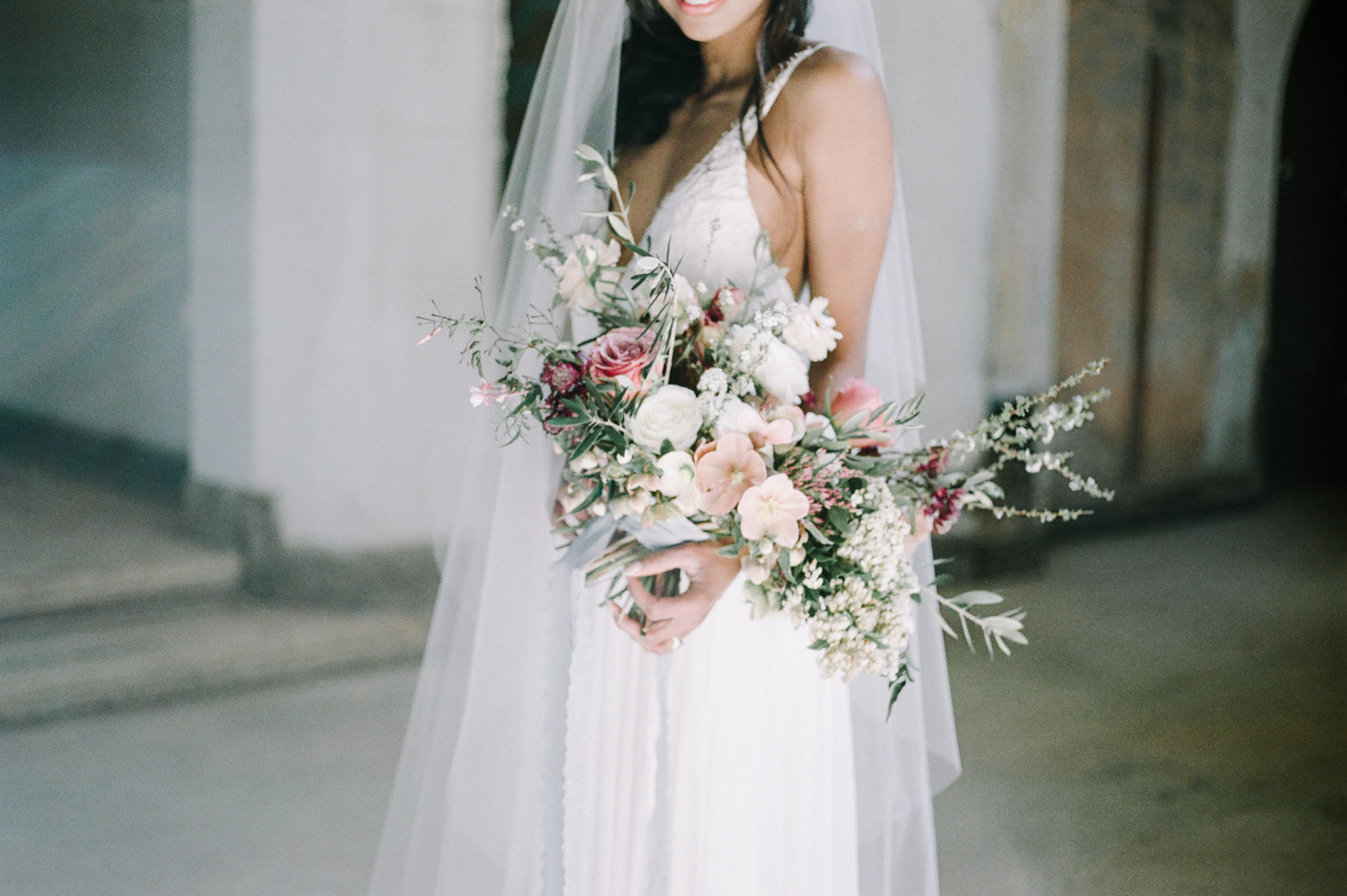A bride holds a lush bouquet of roses, hellebores, and olive leaves in an abandoned cathedral, the location of her destination wedding photos