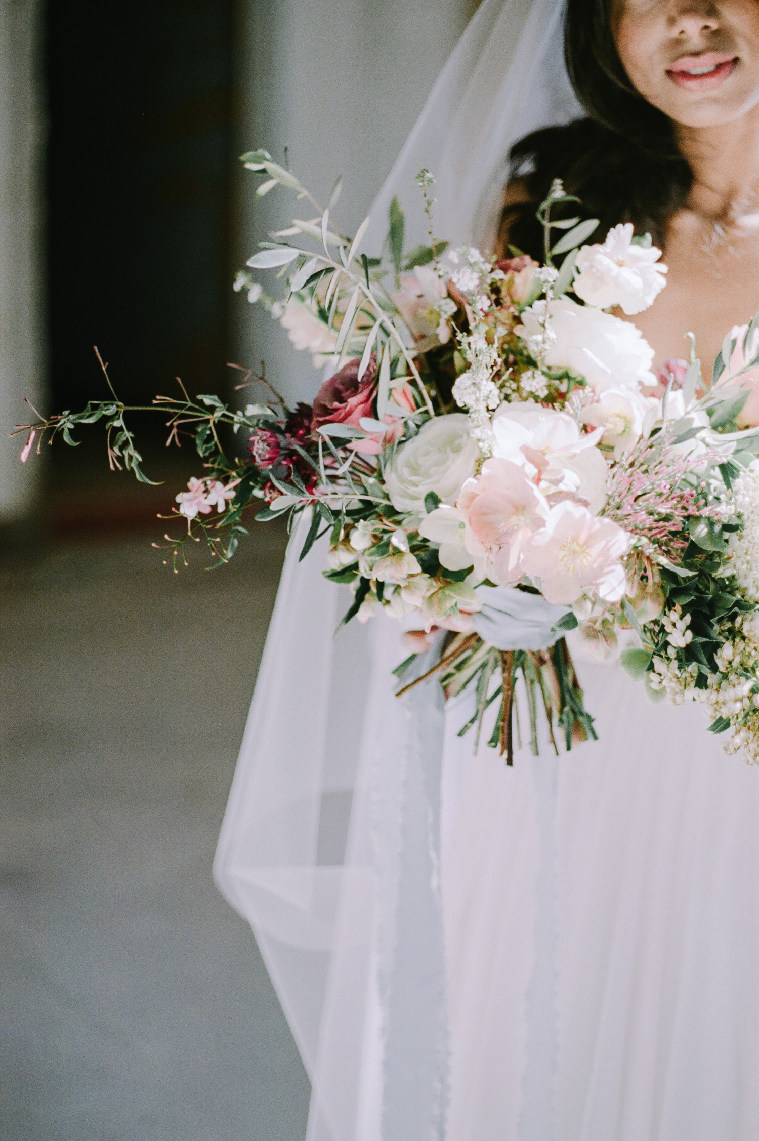 An Indian bride holds a lush wedding bouquet with roses, hellebores, and olive leaves in Detroit
