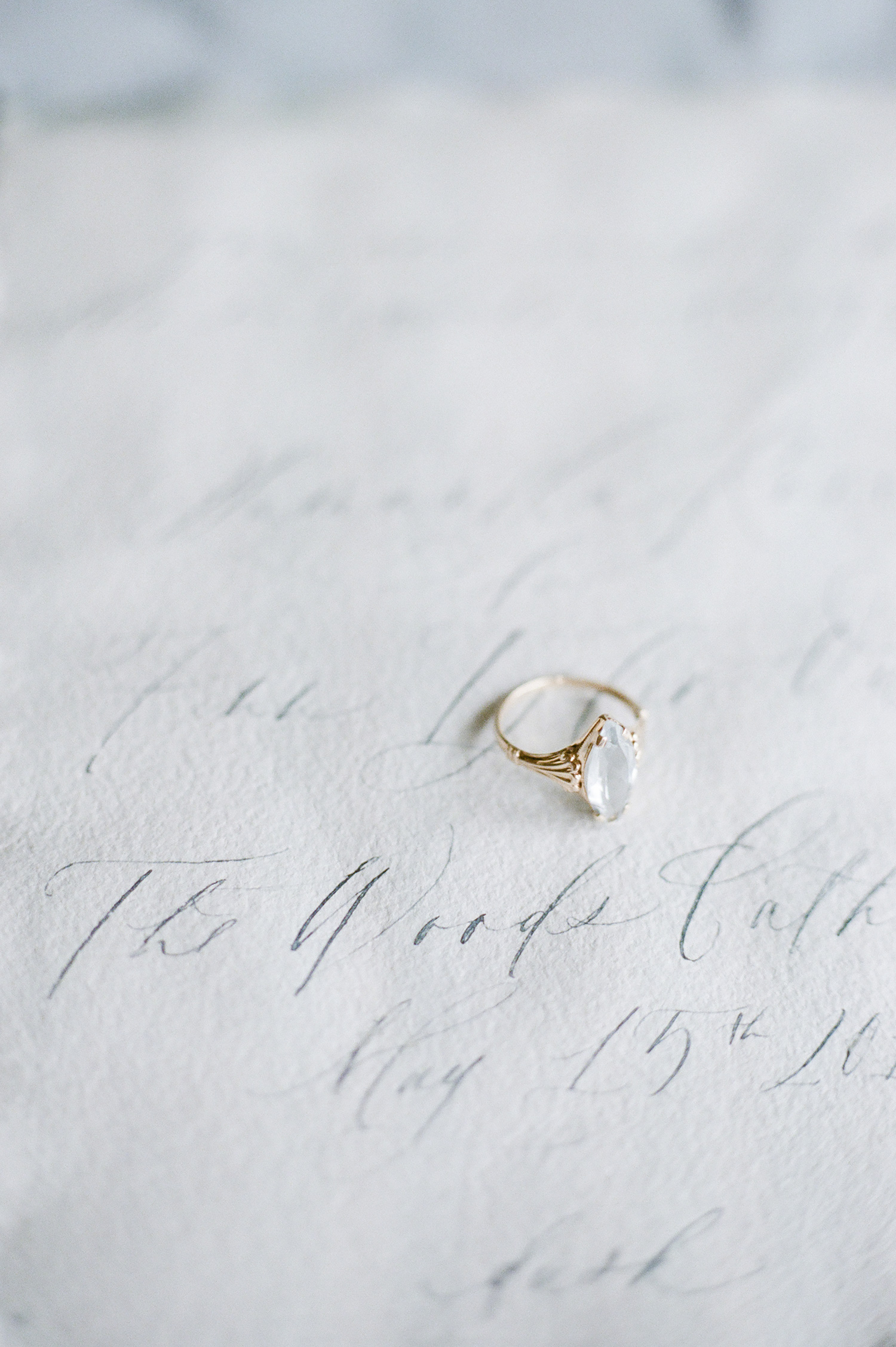 An antique marquise aquamarine and yellow gold ring rests on a blue handmade paper and calligraphy destination wedding invitation