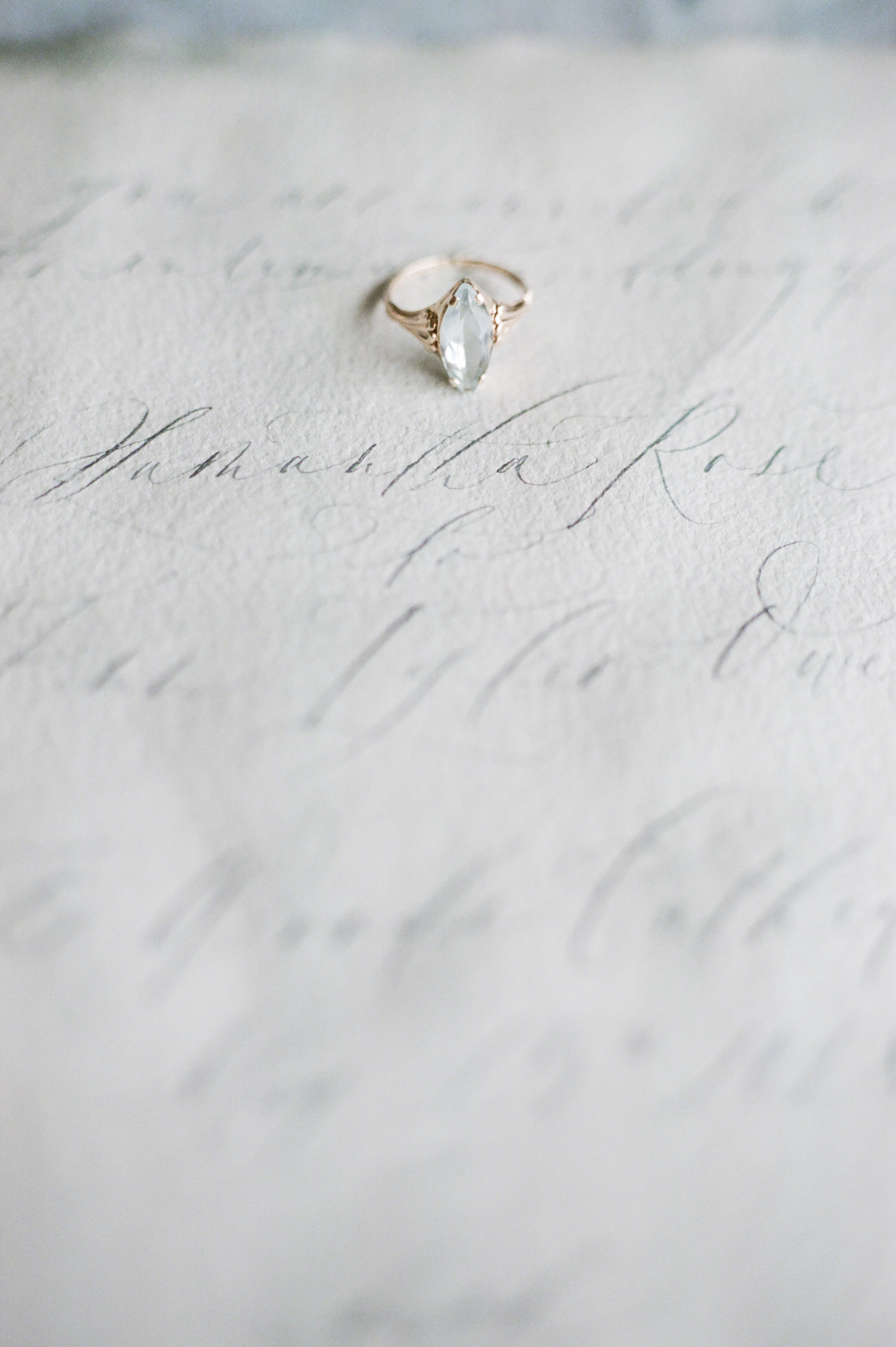 A beautiful antique gold and aquamarine engagement ring rests on a destination wedding invitation