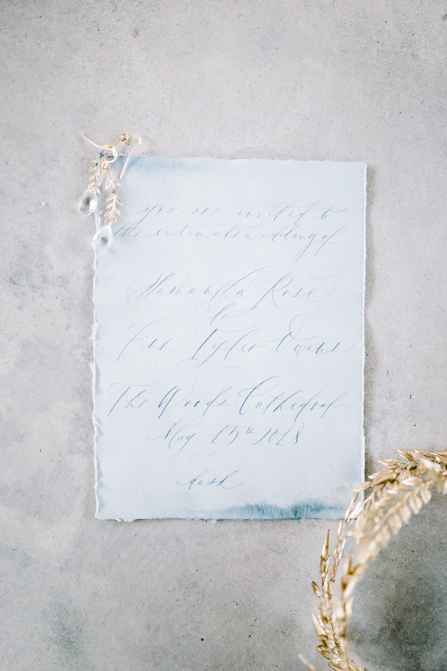 A blue watercolor and calligraphy handmade paper wedding invitation for a destination wedding in an abandoned cathedral, a few pieces of gold wedding jewelry nearby