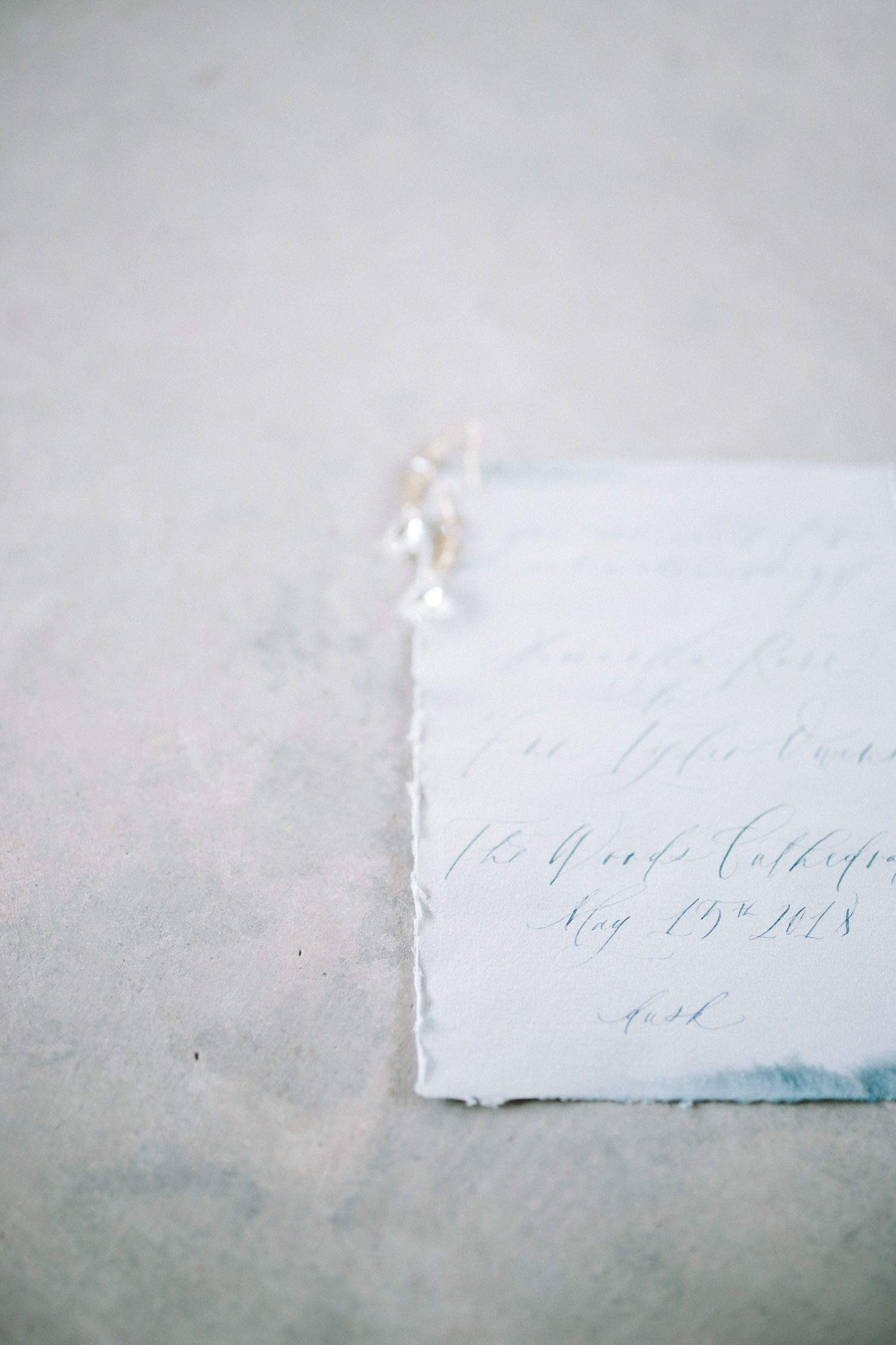 A blue watercolor destination wedding invitation with calligraphy and handmade paper for a Mediterranean destination wedding