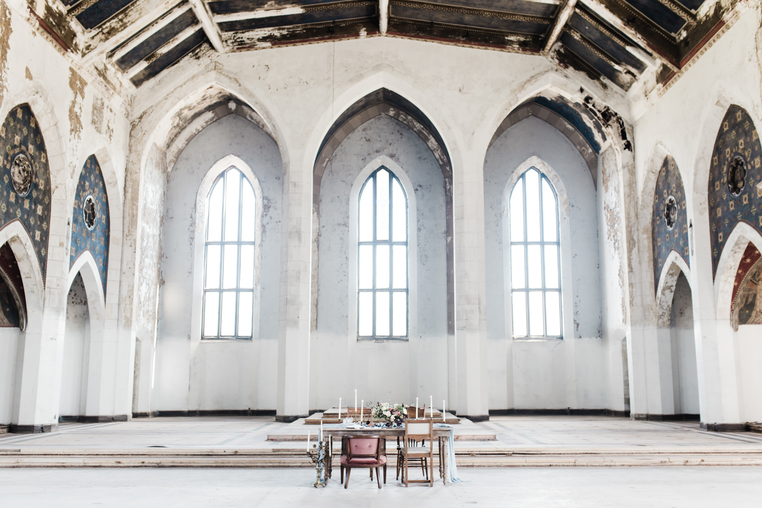 A wedding reception table sits in an abandoned cathedral in Detroit