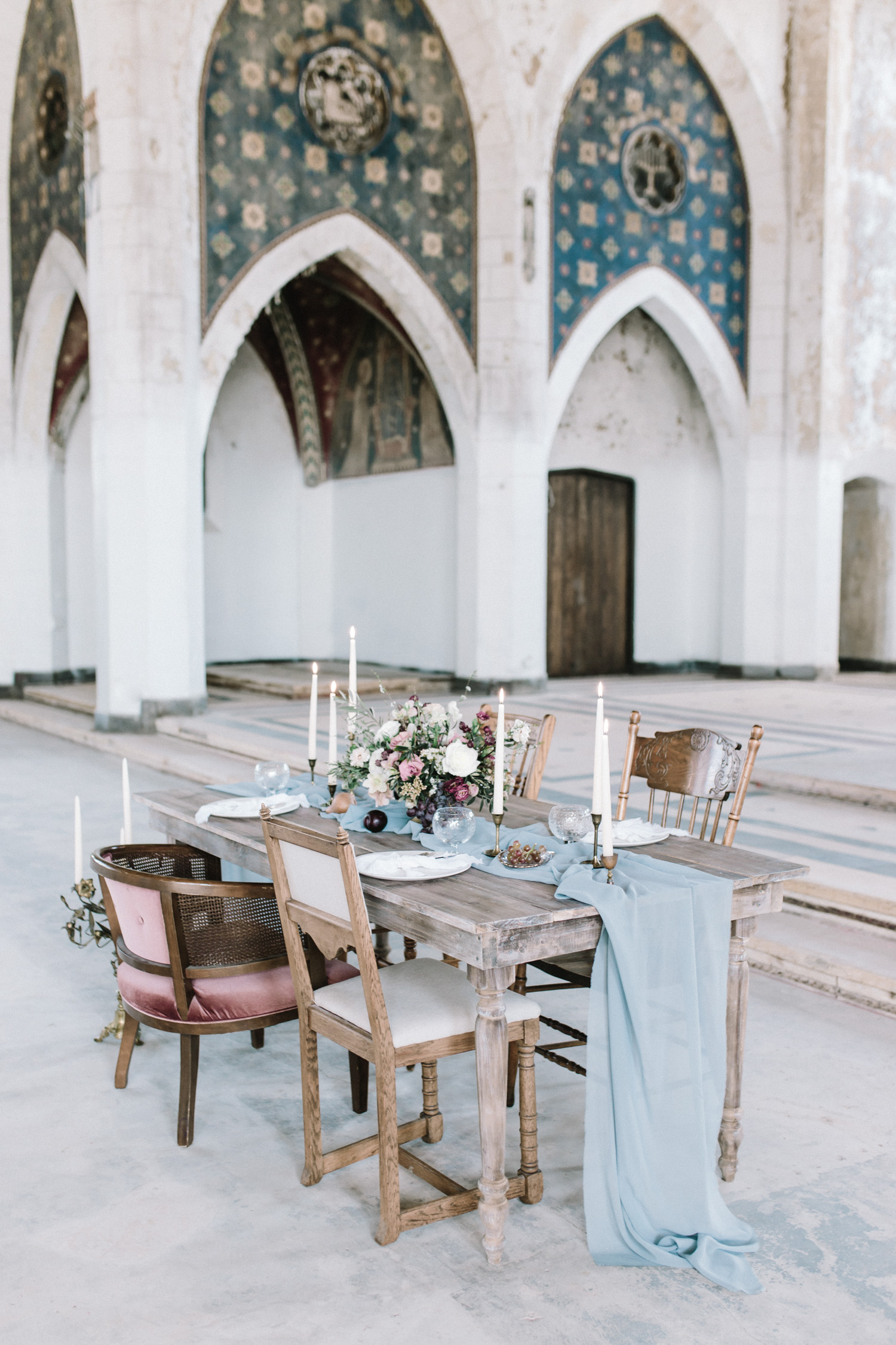 A destination wedding reception table design in an abandoned cathedral