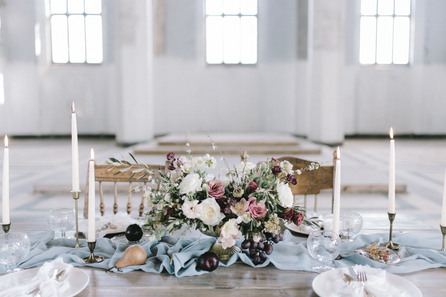A wedding reception table in an abandoned cathedral with a floral centerpiece with grapes