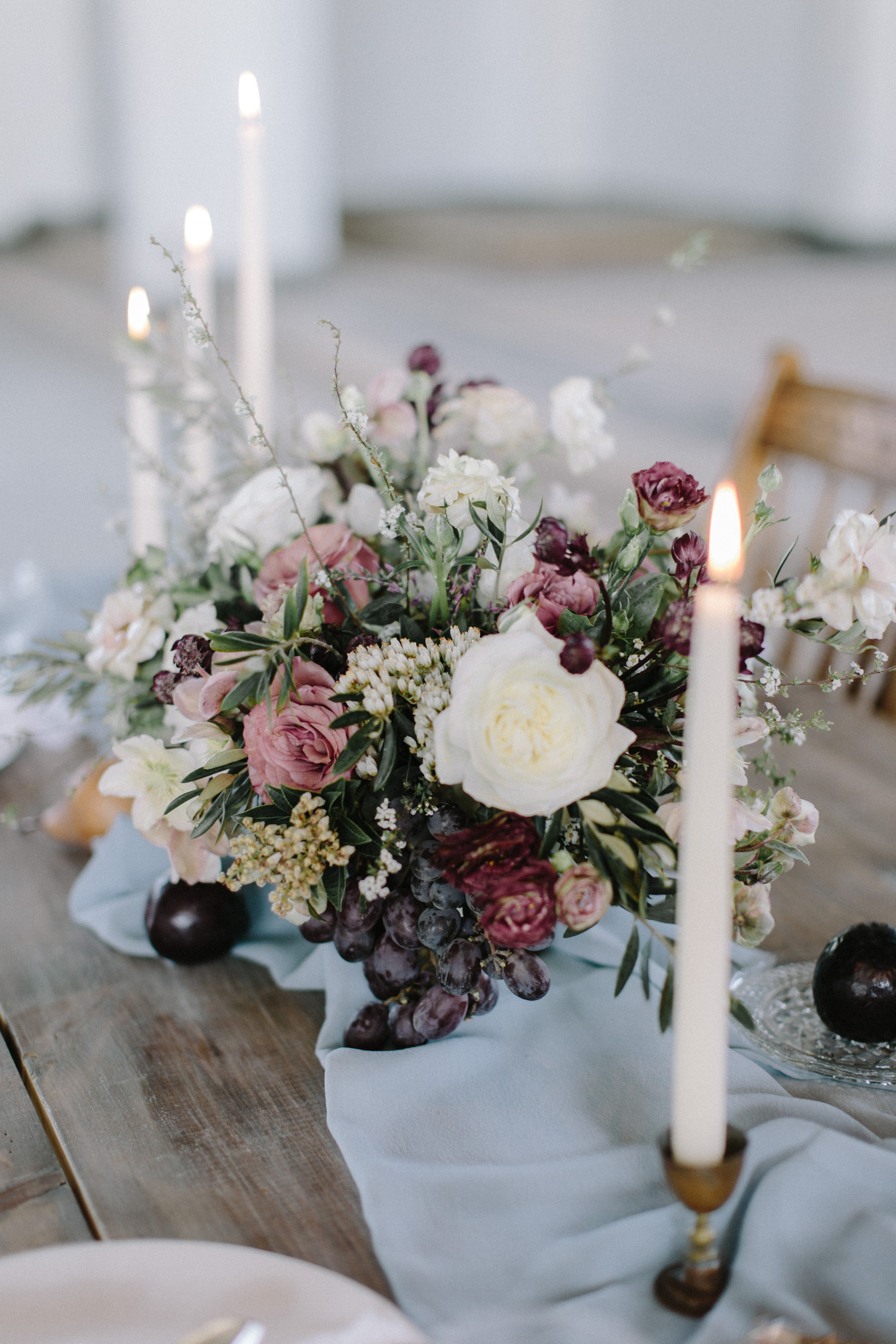 A lush floral centerpiece rests on a wood table with candles in a Detroit cathedral wedding venue