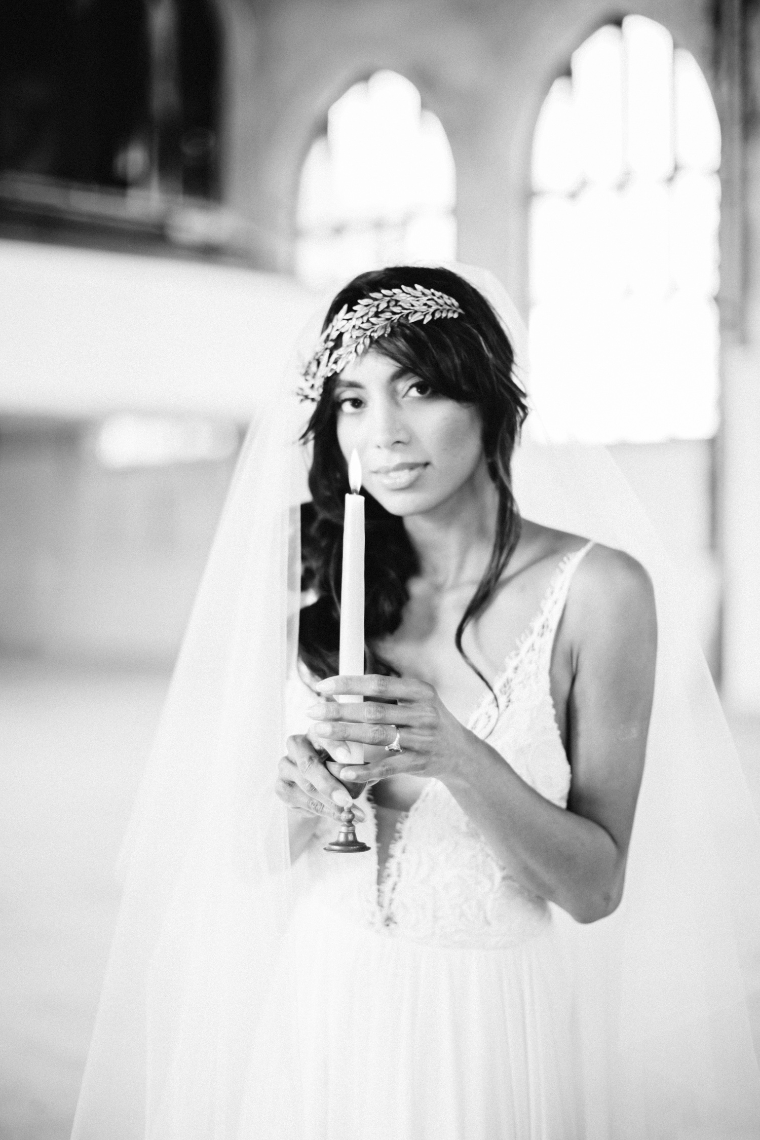 A beautiful Indian bride in a gold, Greek inspired headpiece holds a candle while at her destination wedding in an abandoned cathedral