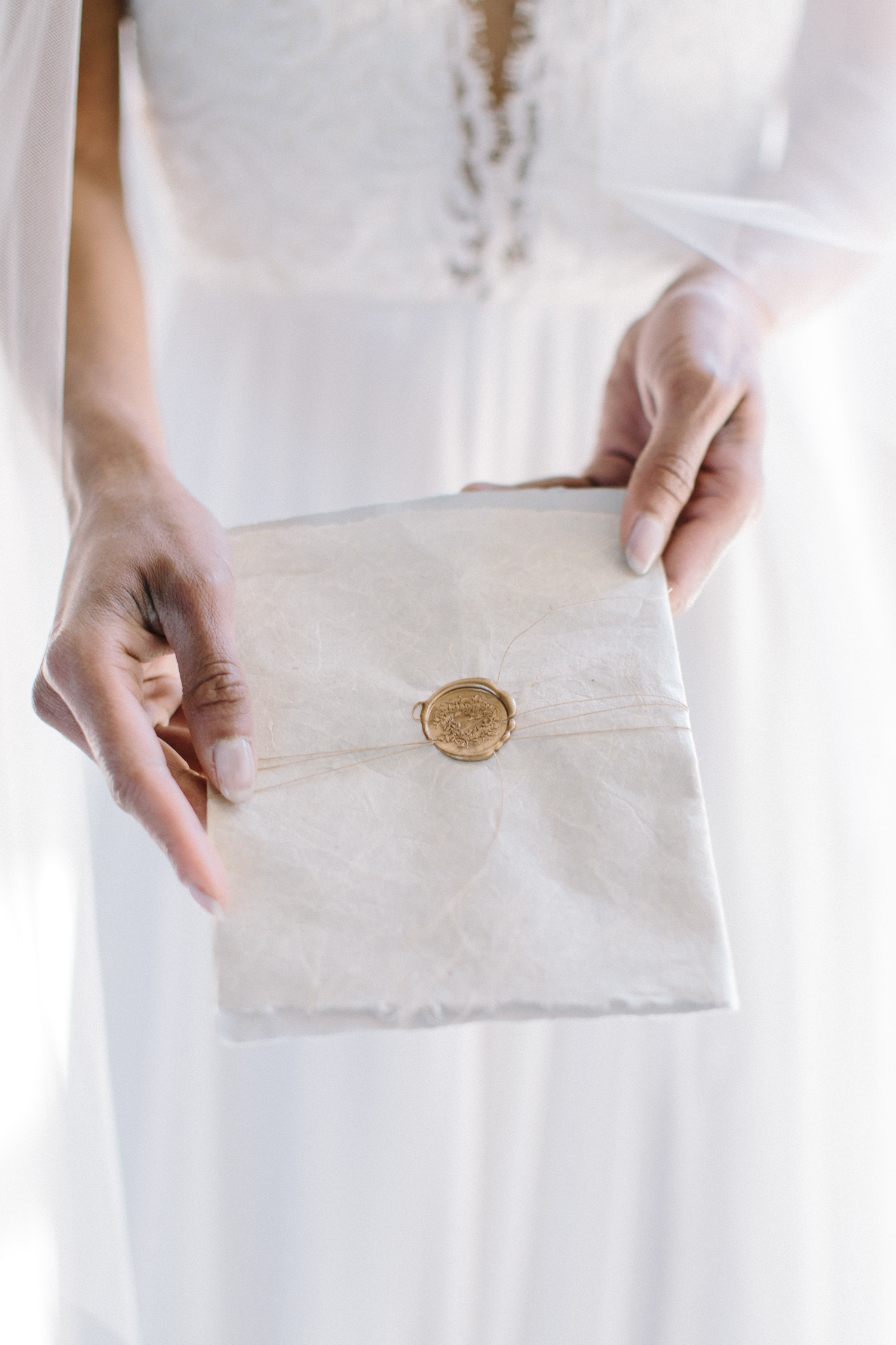 A bride holds out beautiful handmade paper wedding invitation with a gold wax seal in Detroit