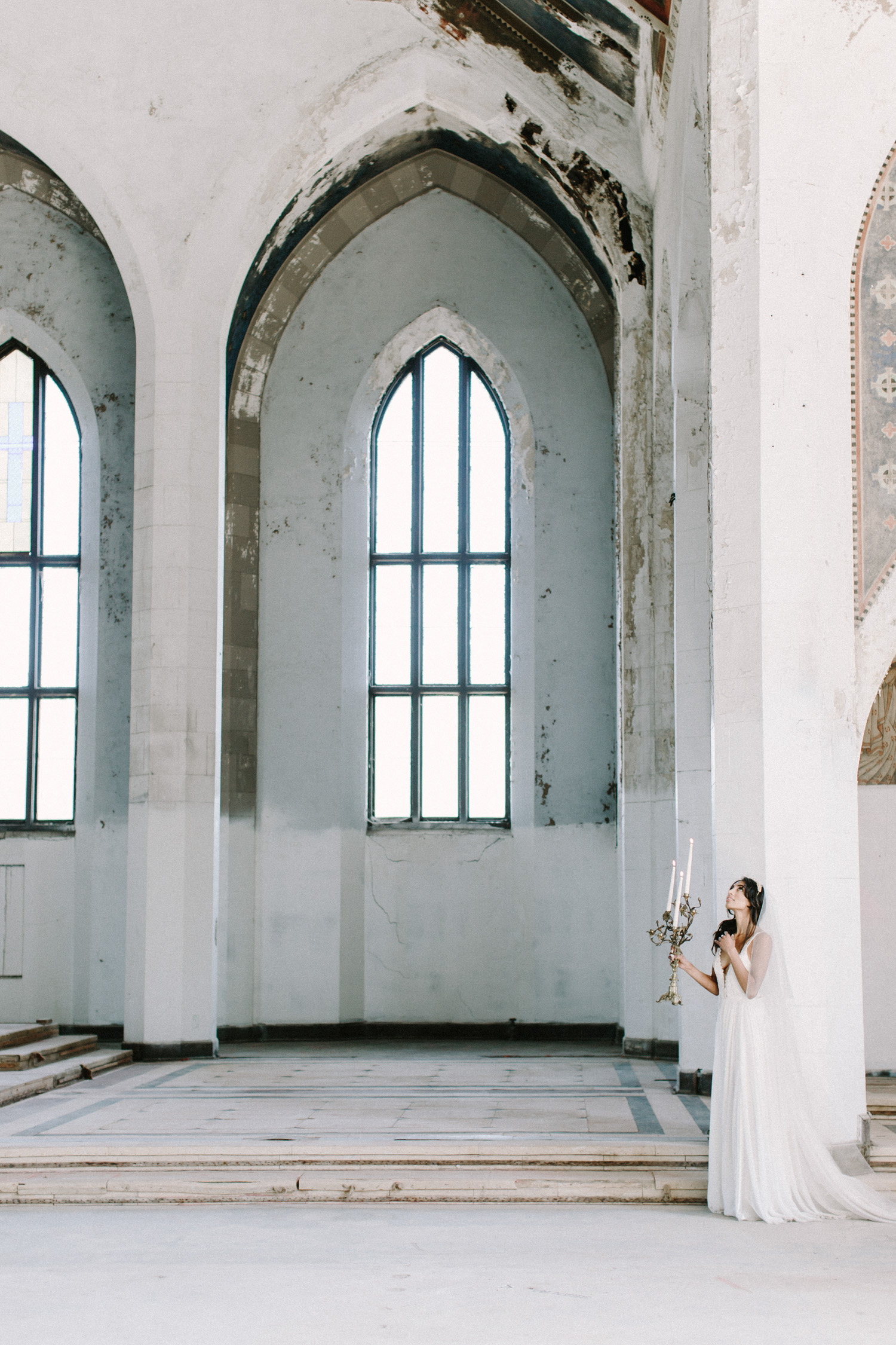 A bride holding a gold candelabra looks up in the abandoned cathedral location of her destination wedding