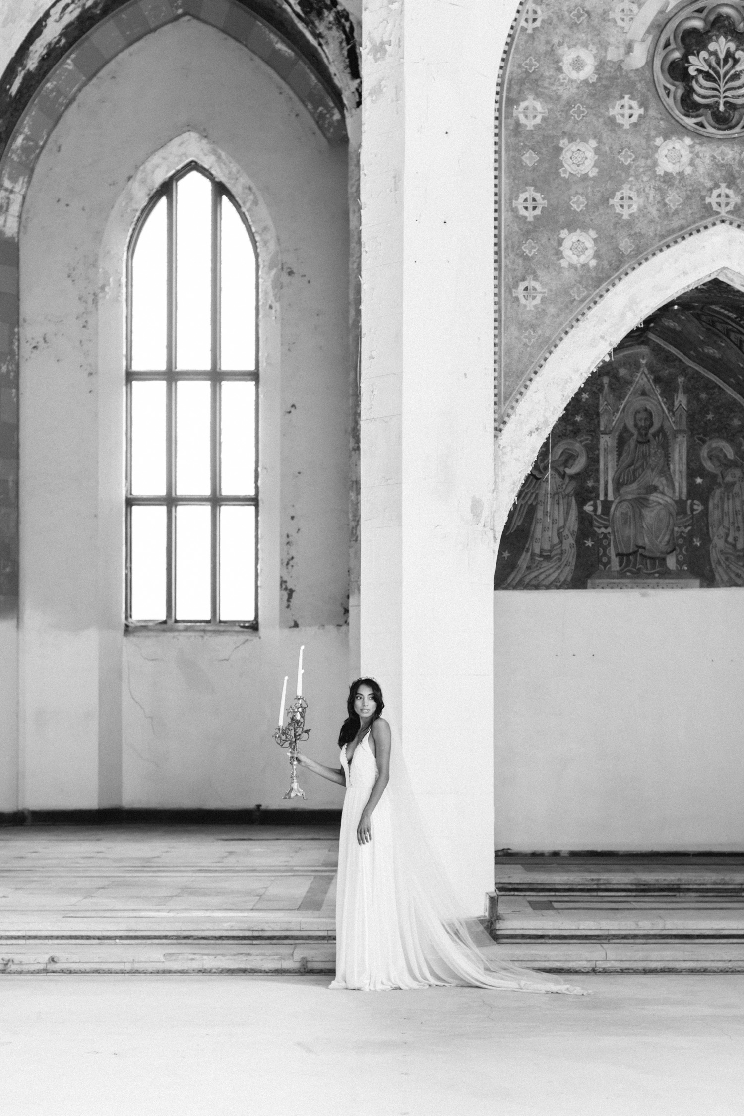 An Indian bride holds an ornate candelabra while exploring an abandoned cathedral in Michigan