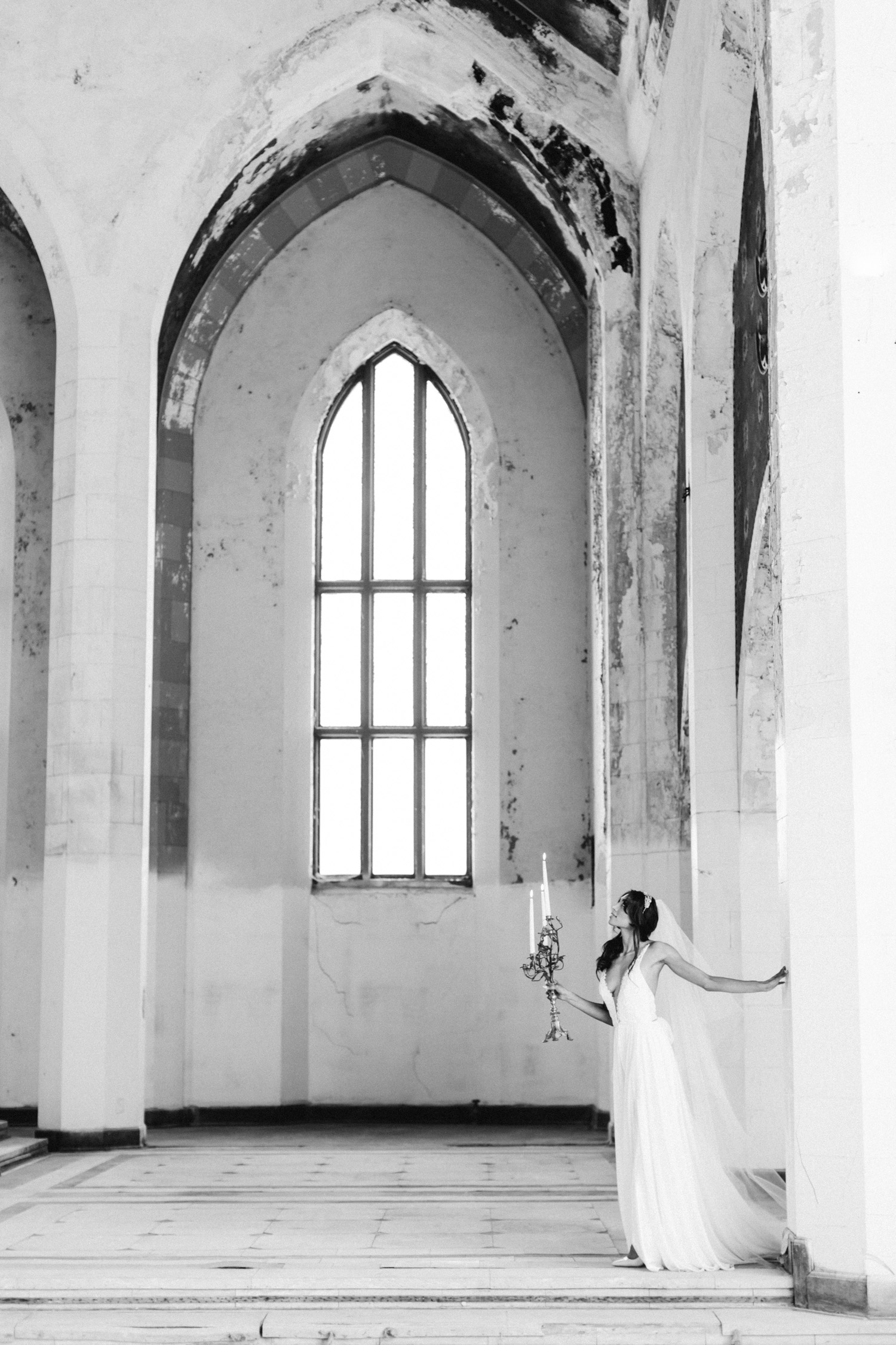 A bride explores an abandoned cathedral with a candelabra at her destination wedding