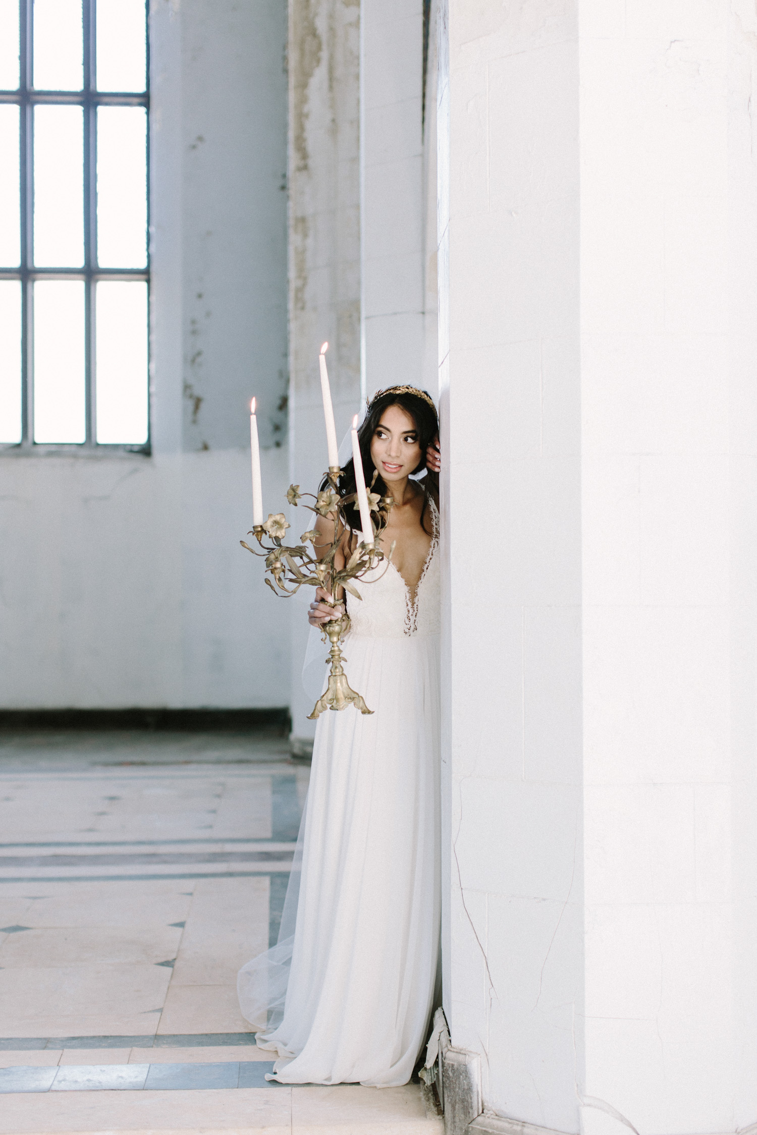 A bride holds a candelabra at her destination wedding in an abandoned cathedral in Detroit