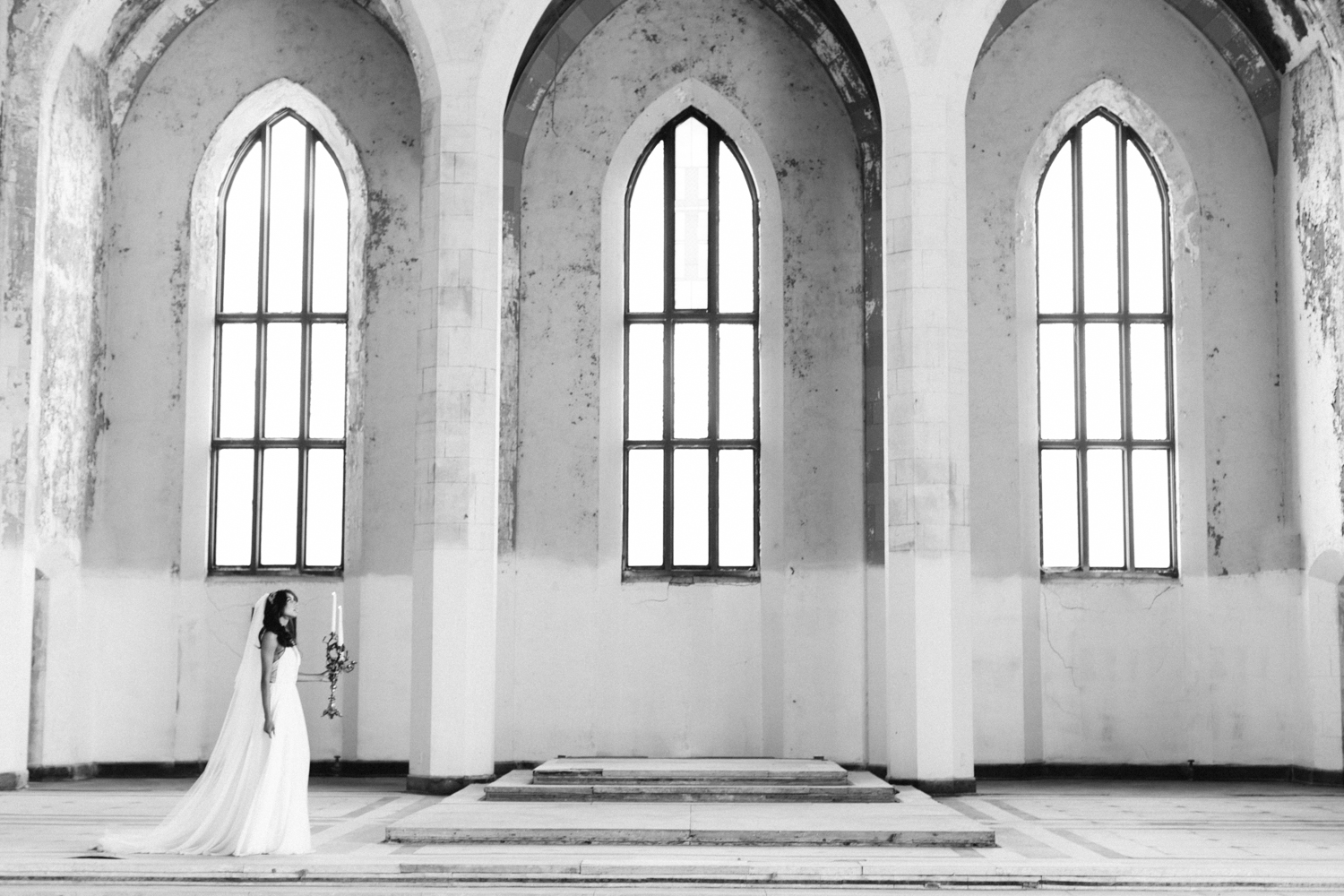 A bride explores the abandoned cathedral location of her destination wedding with an ornate candelabra
