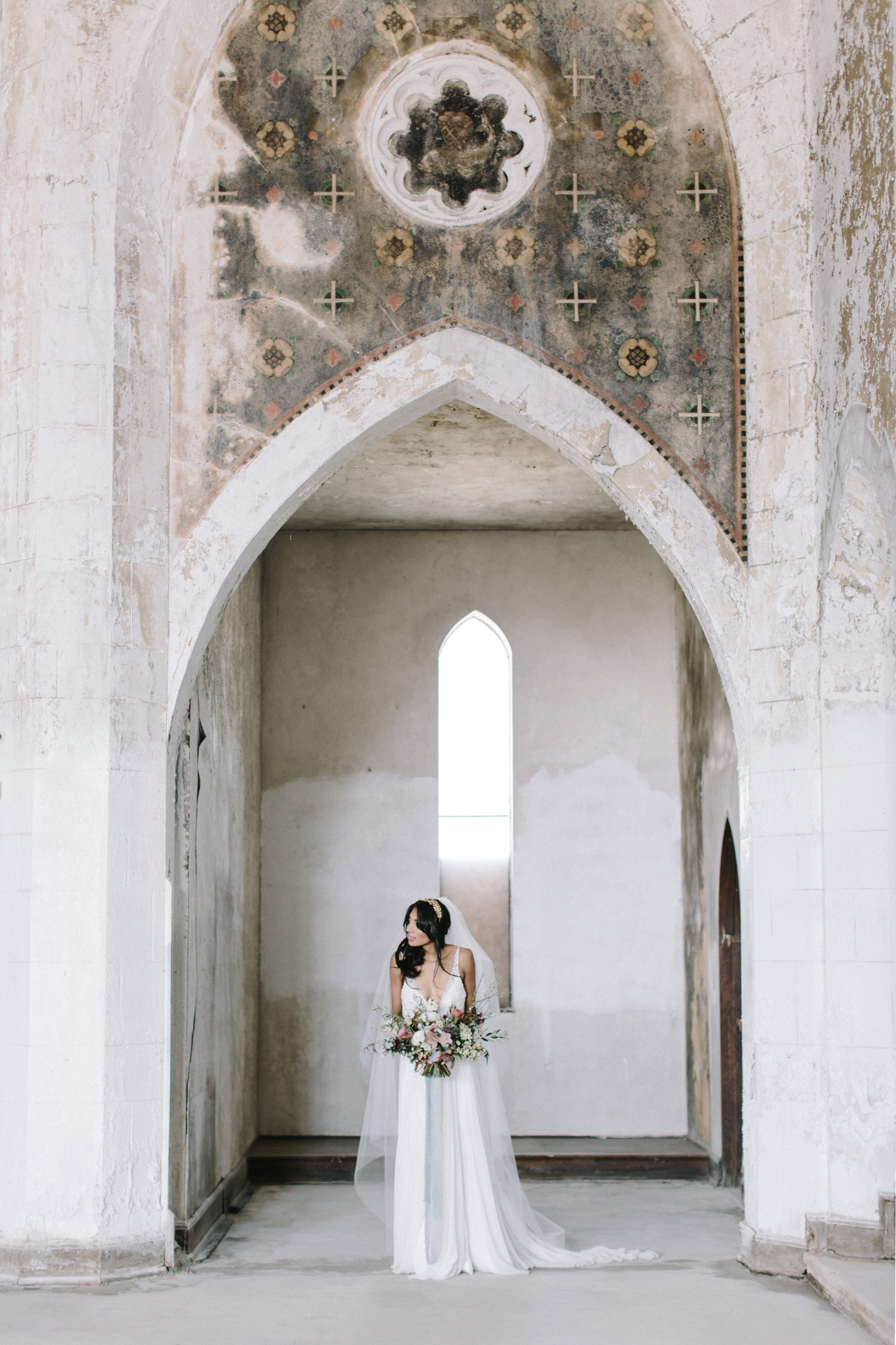 A bride peeks out from under a beautiful arch at her destination wedding in an abandoned cathedral