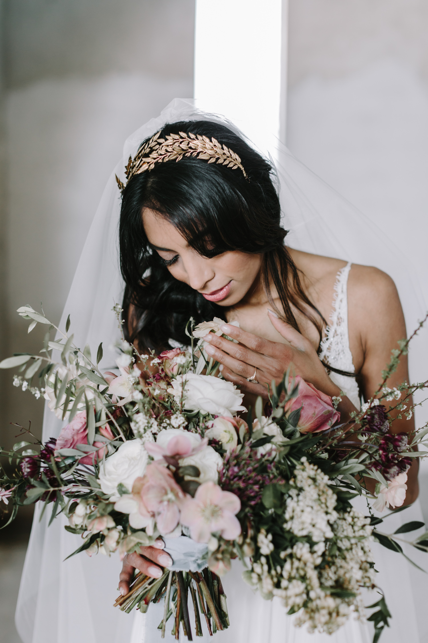 A bride tenderly touches the flowers in her bouquet at her destination wedding
