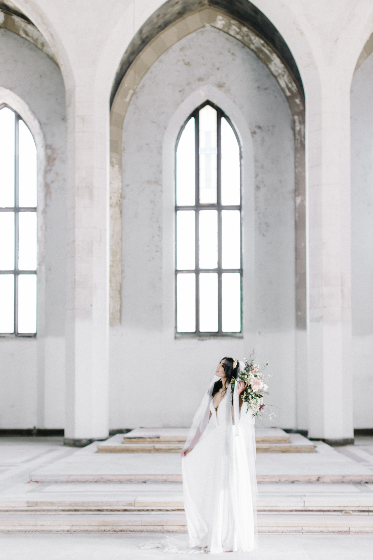 A bride gazes upward while holding her bouquet at her destination wedding in an abandoned cathedral