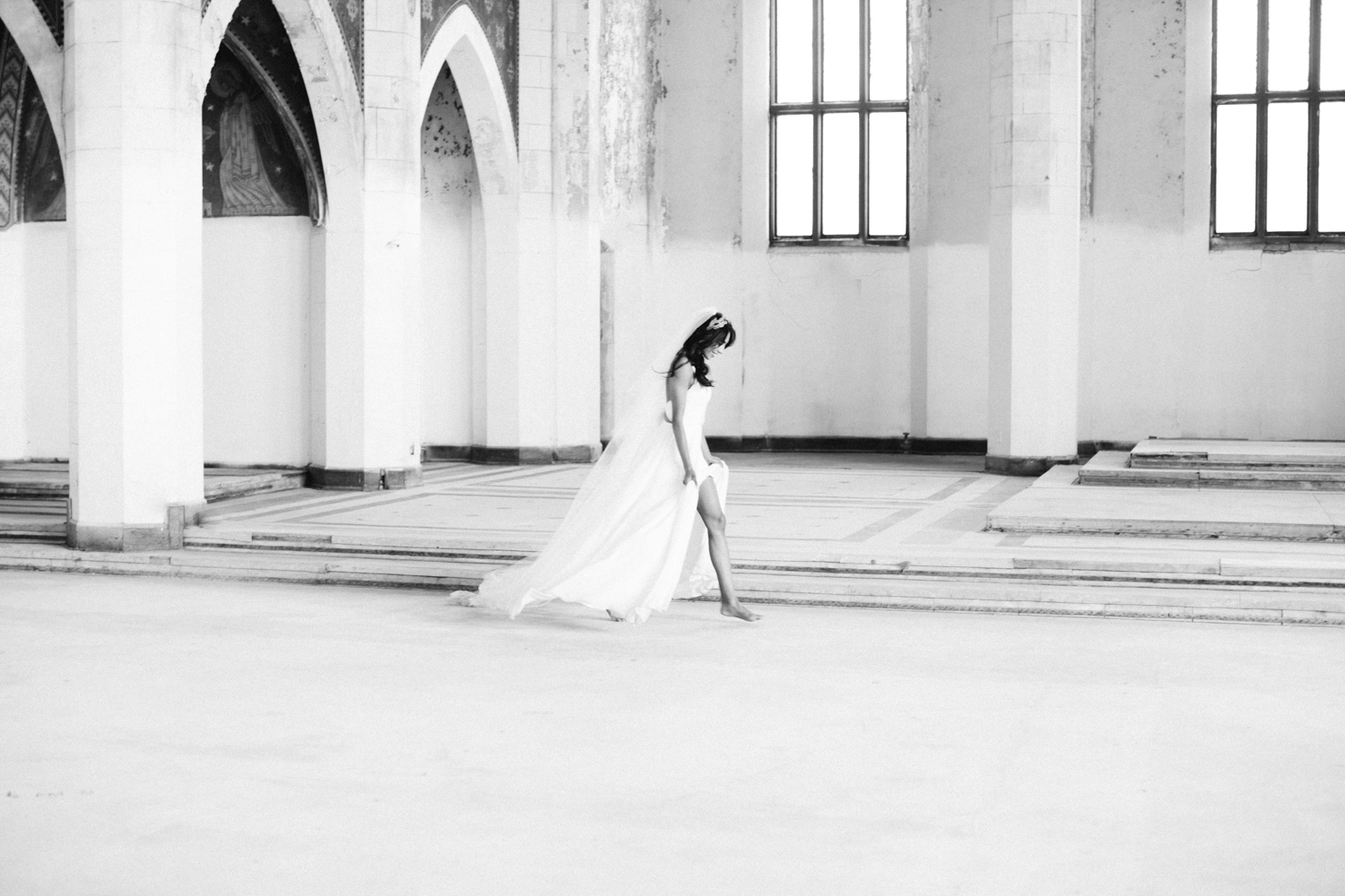 A bride runs through an abandoned cathedral at her destination wedding