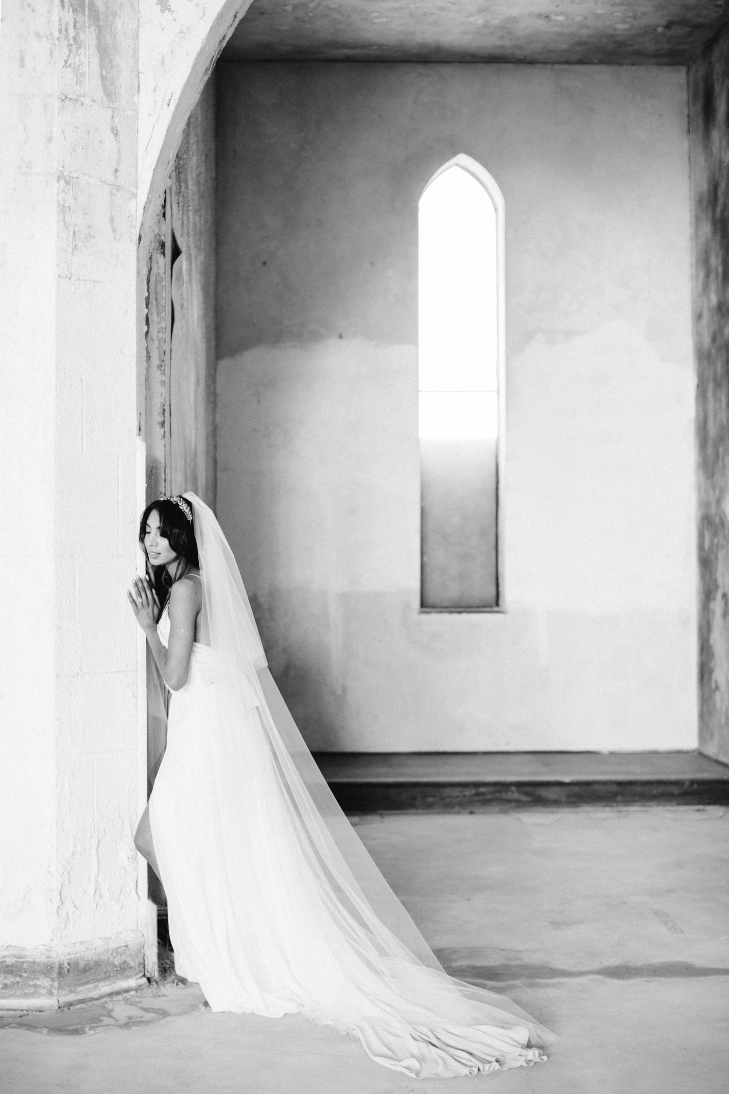 A bride rests against an old, historic wall at her destination wedding in Greece