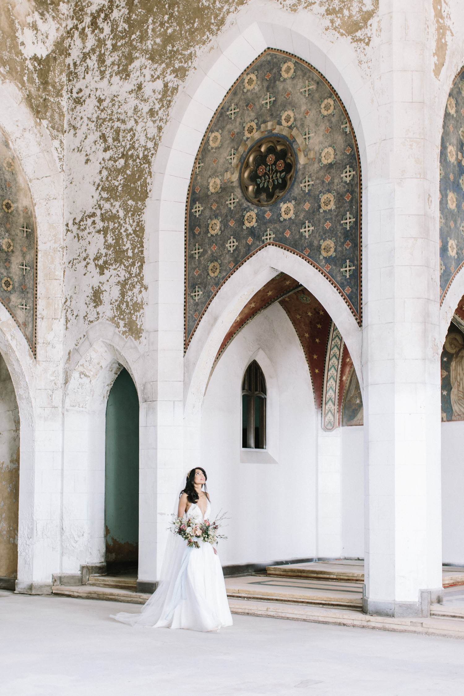 An adventurous bride explores the abandoned cathedral location of her destination wedding in Greece