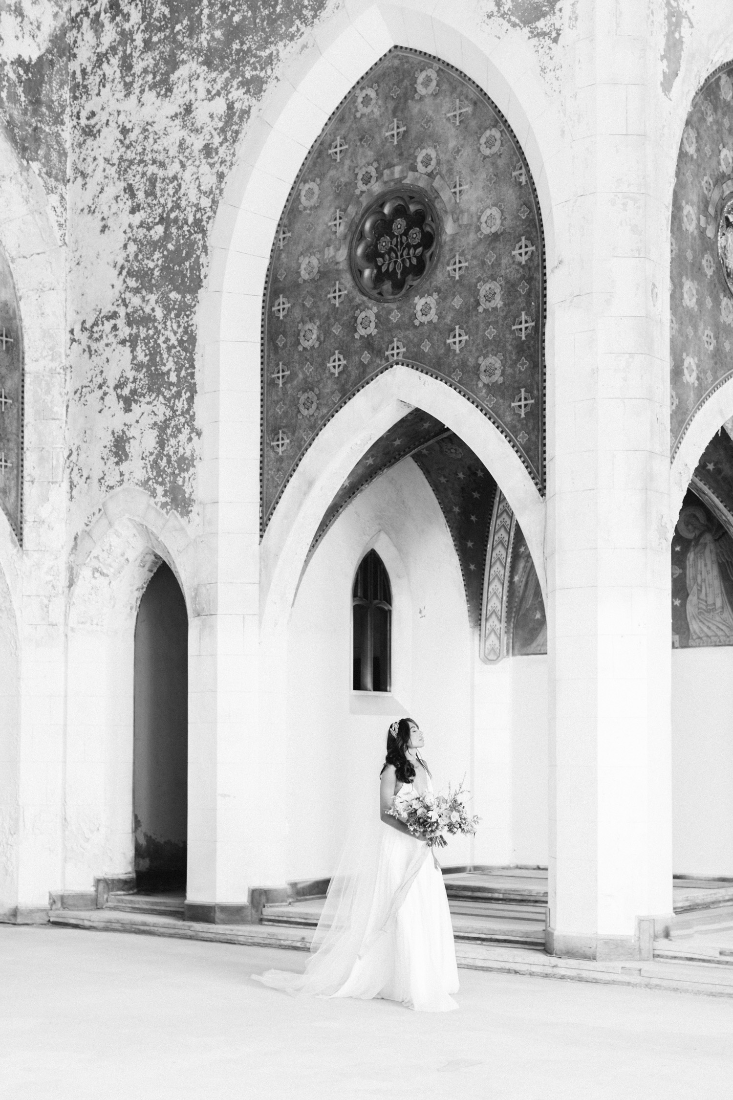 A bride wanders through an abandoned cathedral, the location of her destination wedding