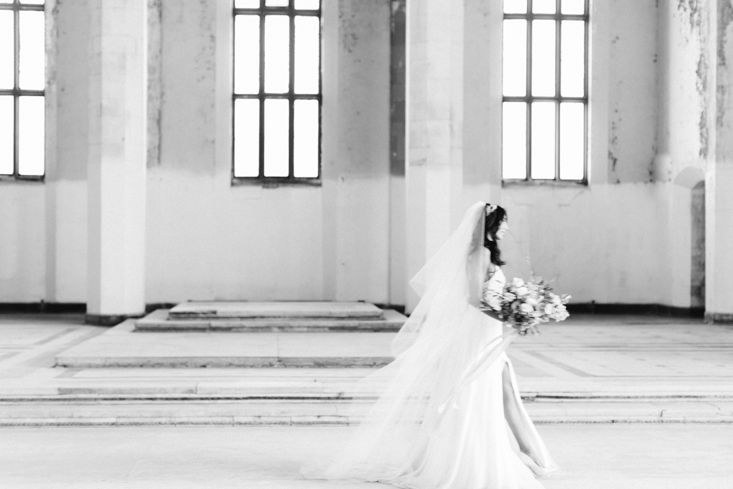 A bride is caught in movement while walking through the abandoned cathedral location of her destination wedding