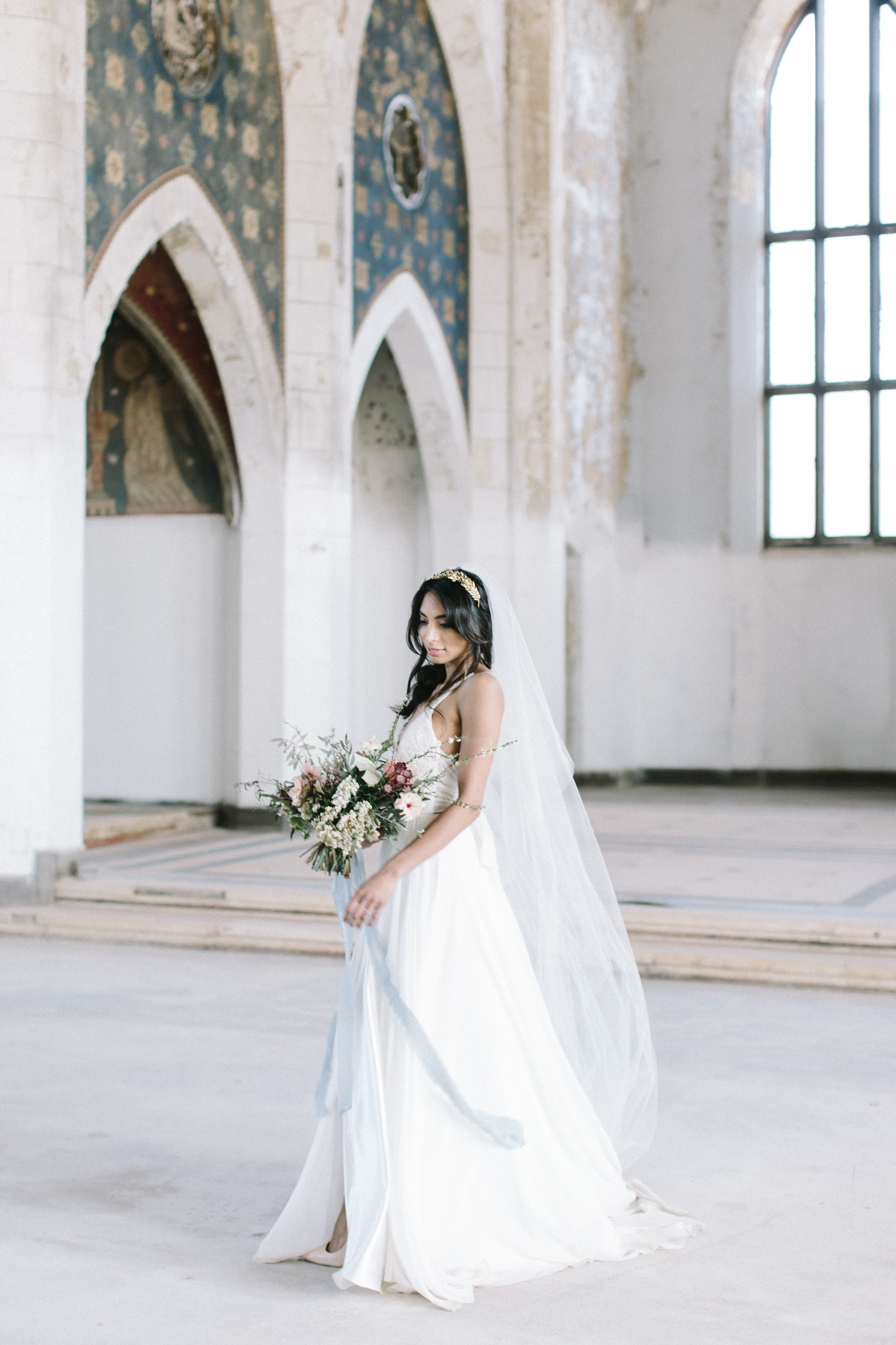 A bride twirls while holding her bouquet at her destination wedding in an abandoned cathedral