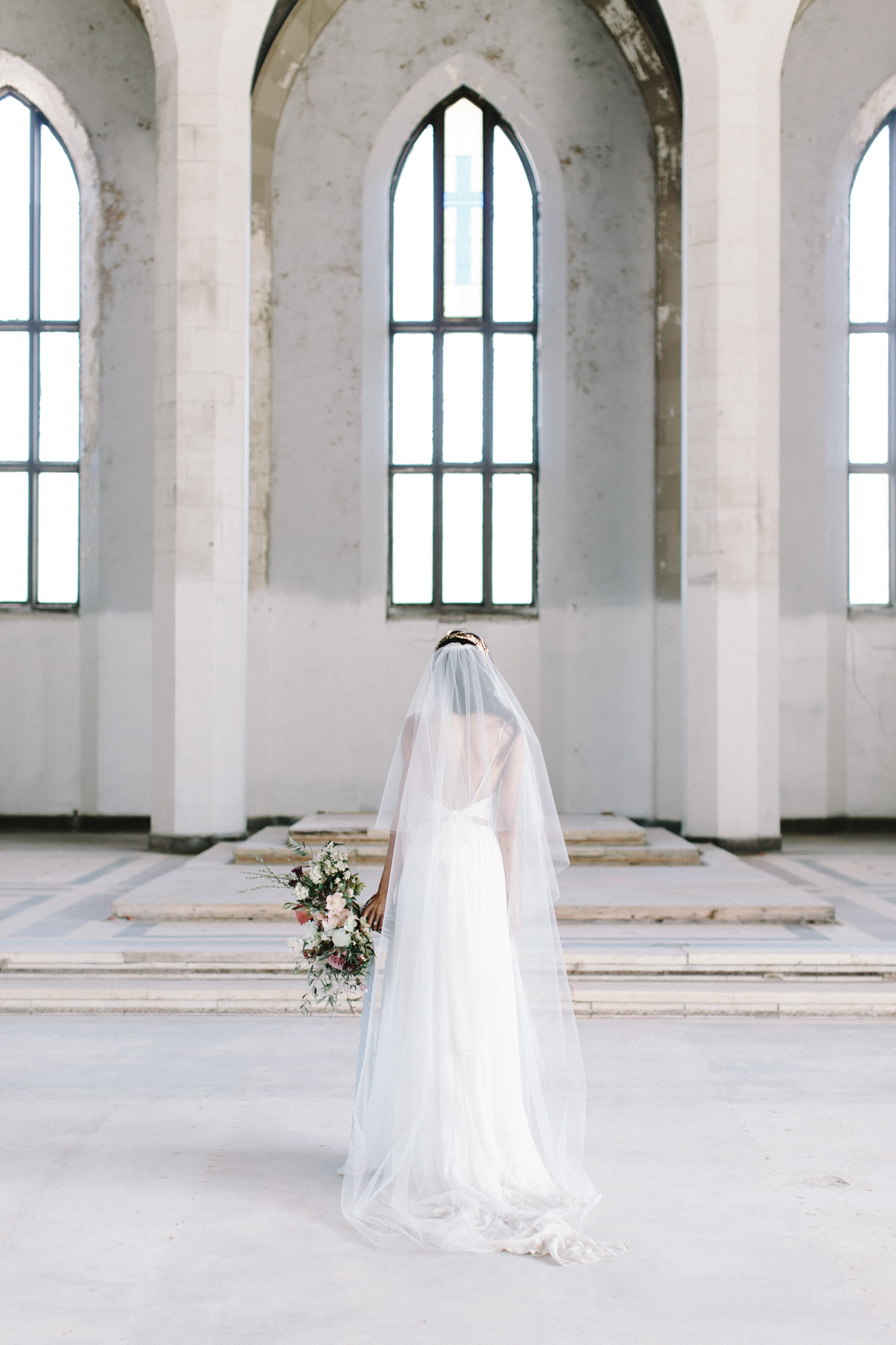 A bride stands alone as she gazes up in an abandoned cathedral, the location of her Greece destination wedding