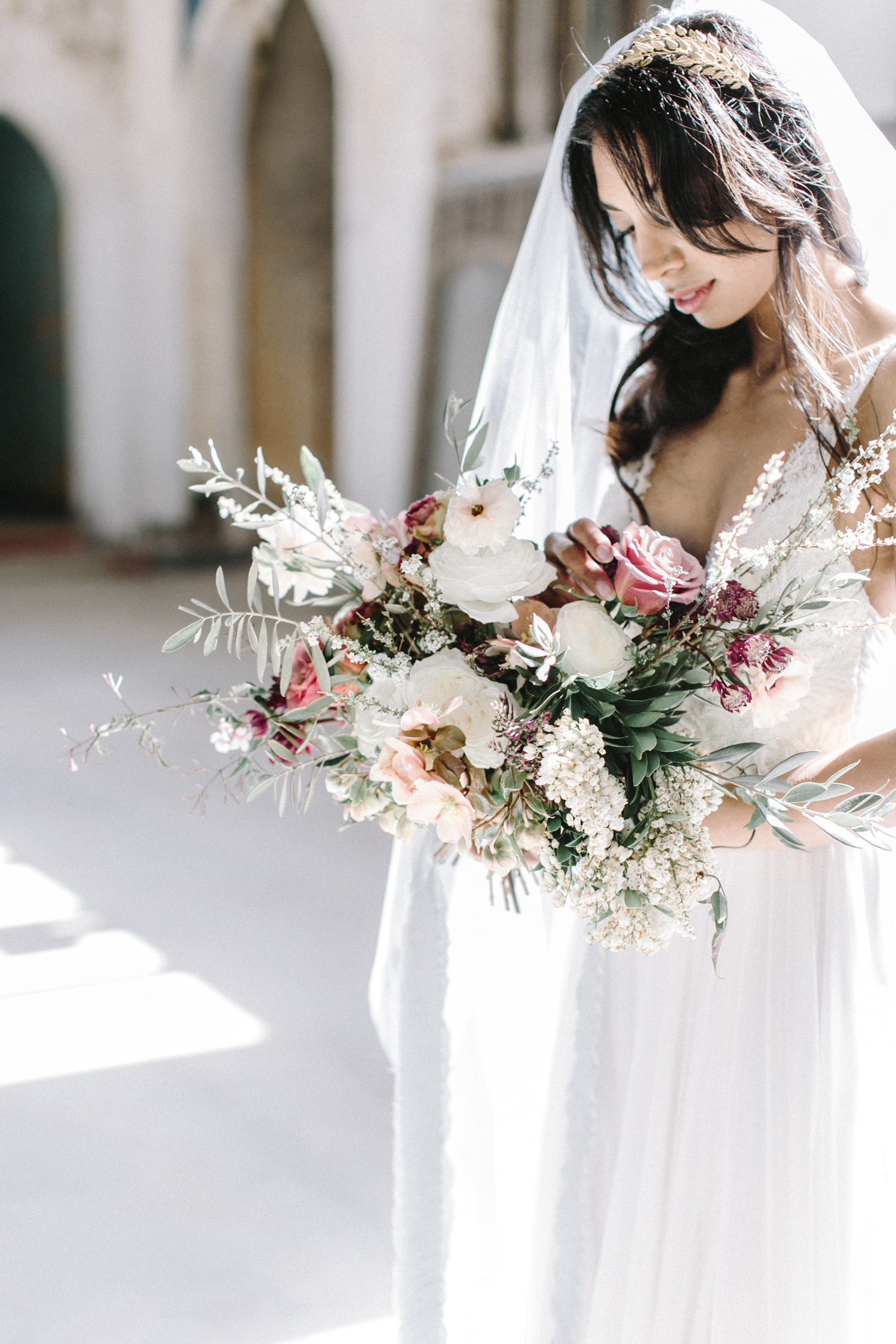 A bride holds her bouquet in sunlight at her destination wedding