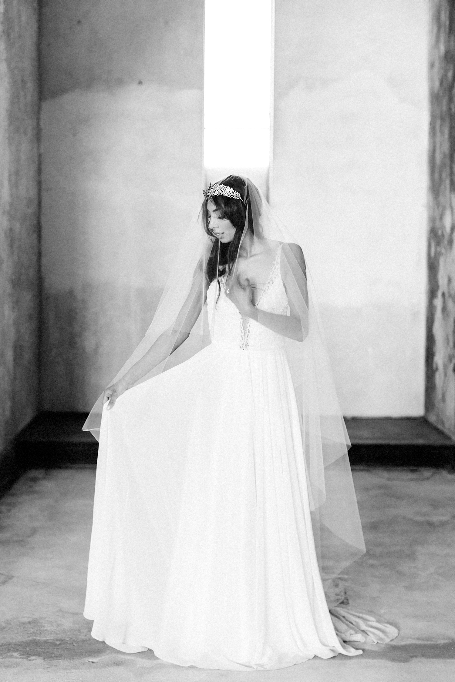 A bride in a long veil and gold headpiece at an abandoned cathedral, the location of her destination wedding