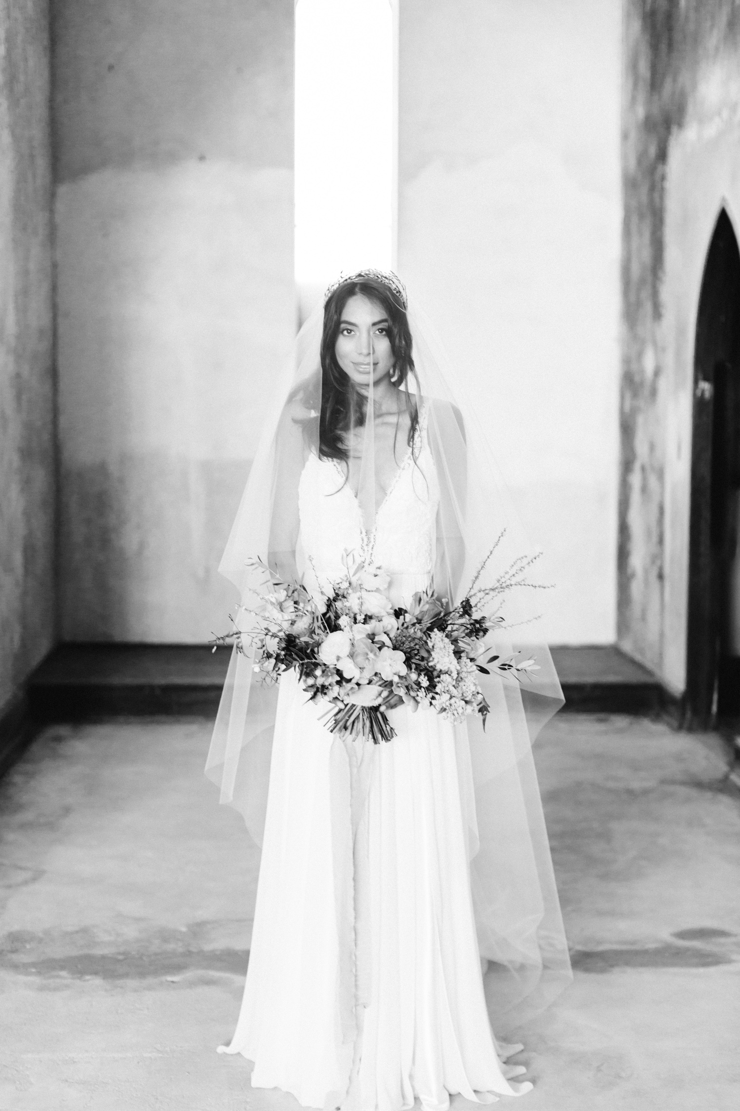A bride with a bouquet and long veil at her destination wedding in an abandoned cathedral in Greece