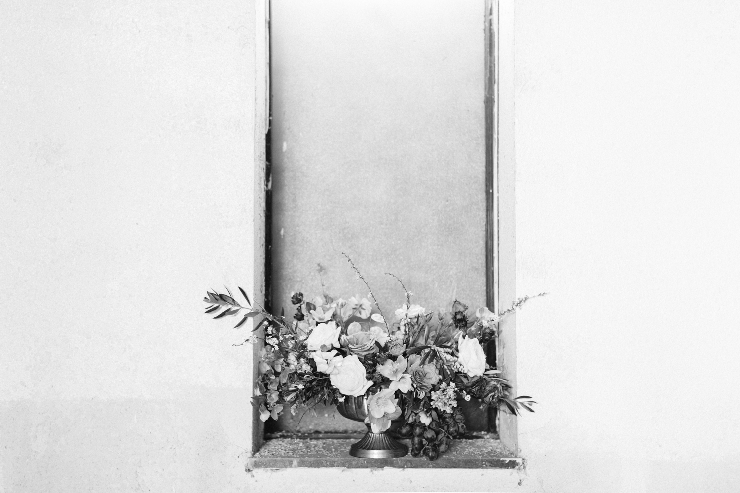 A floral arrangement rests in the window of an abandoned cathedral at a destination wedding