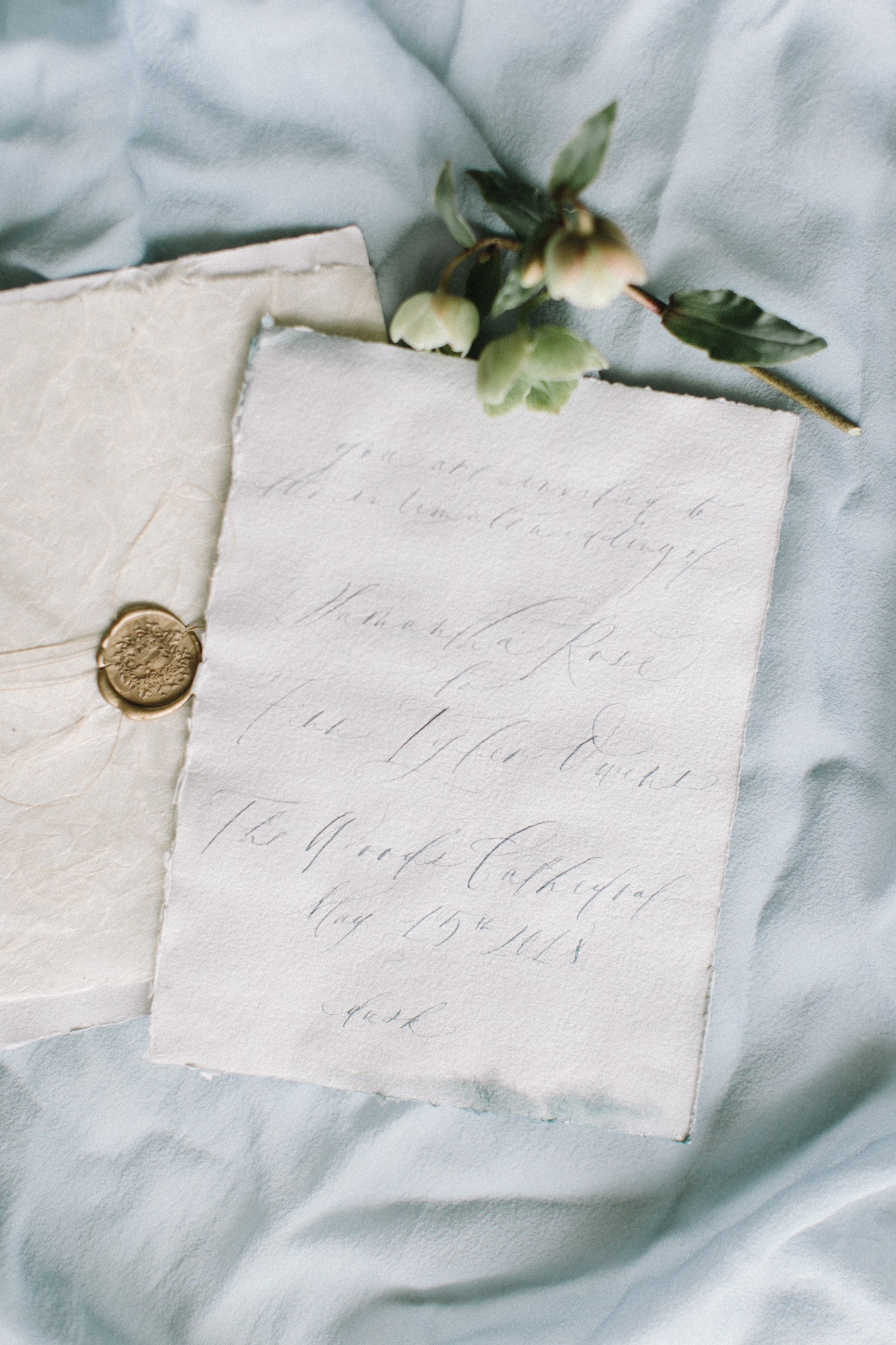 A blue handmade paper and calligraphy wedding invitation with a gold wax seal rests on light blue silk at a destination wedding