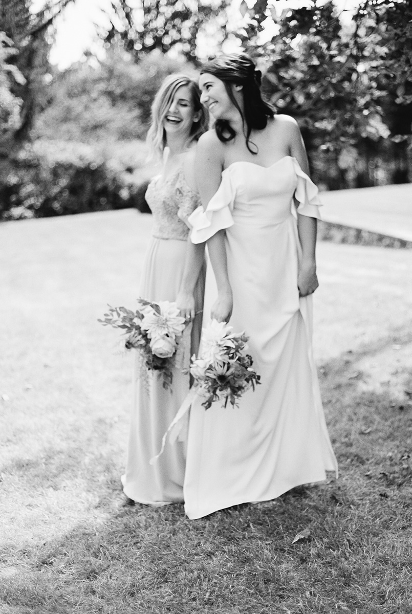 two bridesmaids laugh together at a wedding at Greencrest Manor in Battle Creek, Michigan
