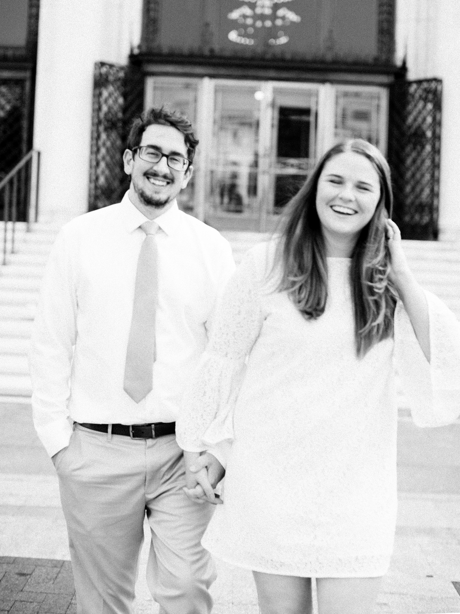 A couple holds hands and laughs in front of the Detroit Institute of Arts during their engagement photo session