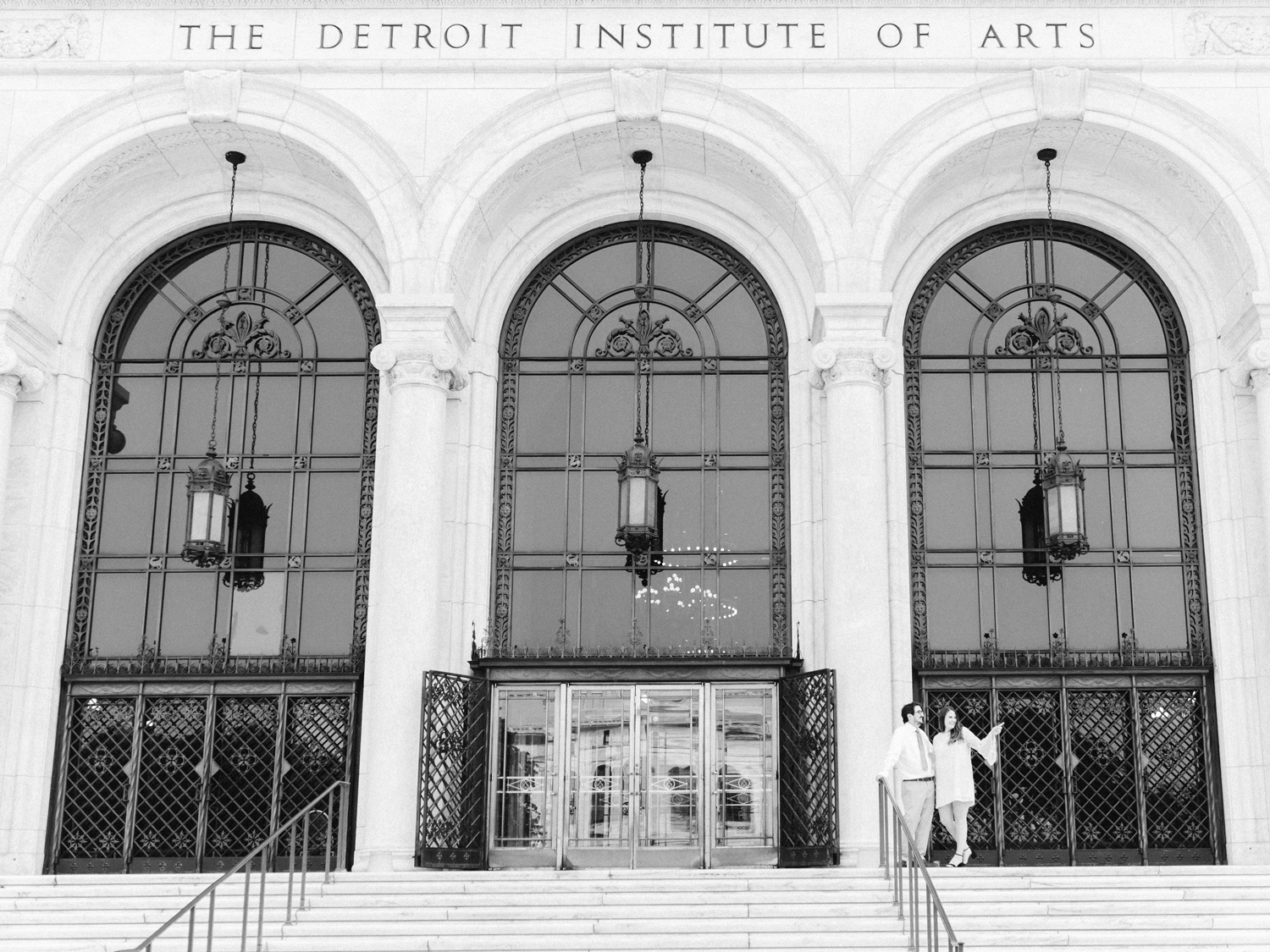 A photo of the Detroit Institute of Arts with an engaged couple together on the steps, the woman pointing as they take in the sights of Woodward Avenue