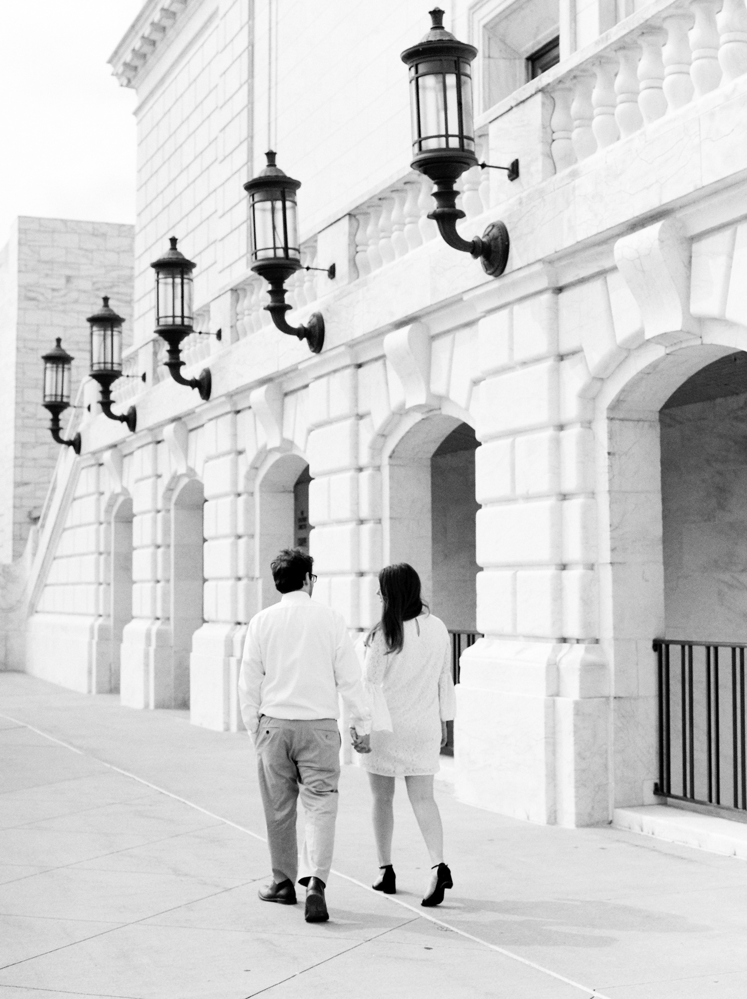 A dressed-up couple walks together outside a beautiful location in Detroit, the DIA, during their engagement photography session